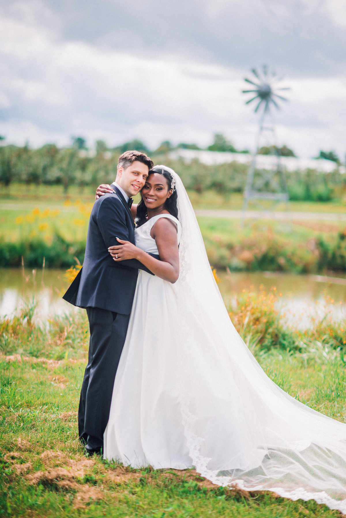 bride and groom embrace by a pond