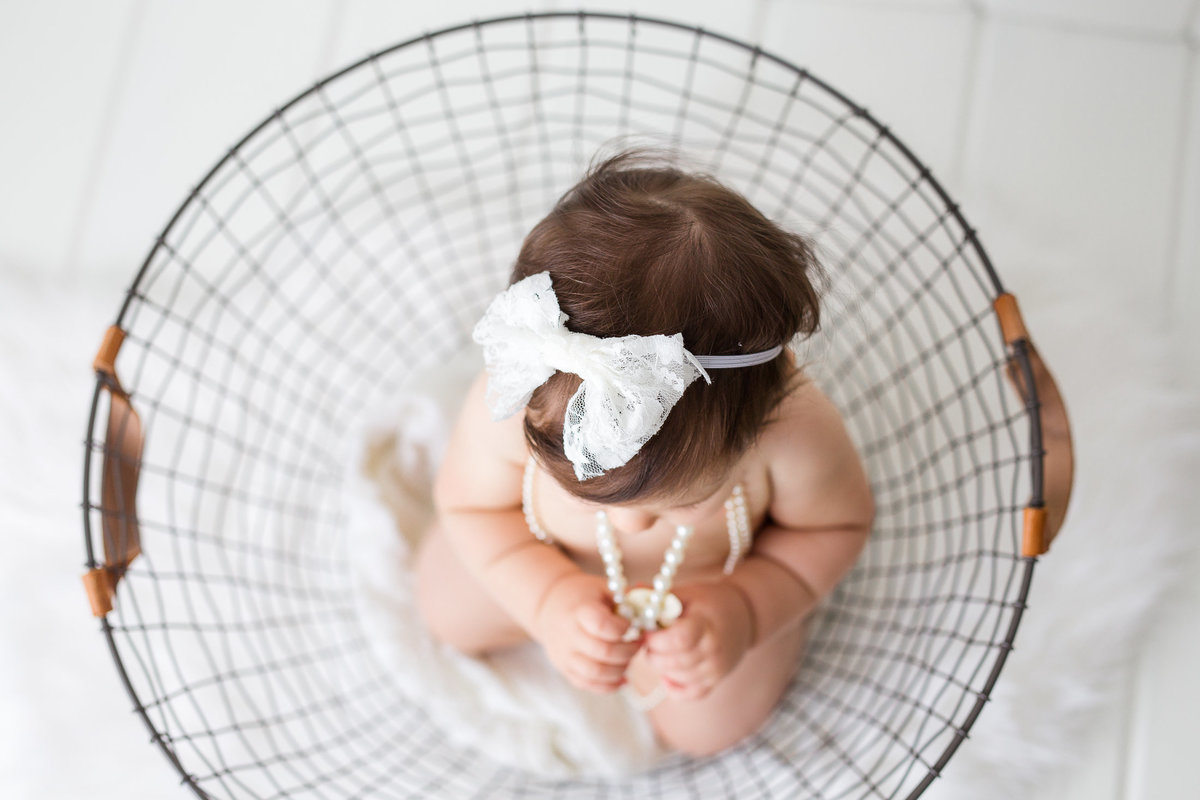 overhead shot of baby girl in wire basket {Oakville Baby Photographer}