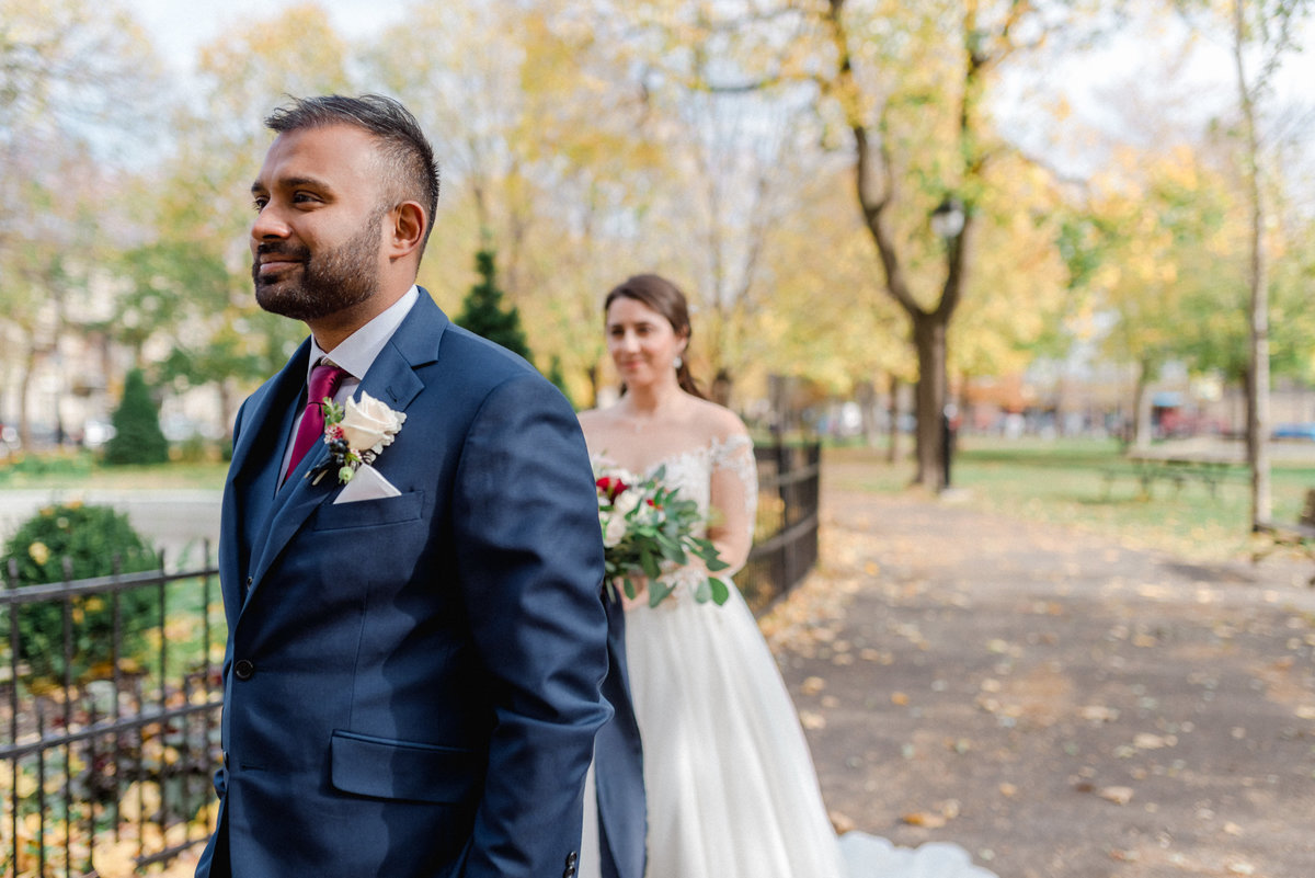 Groom facing away from approaching bride in Navy Suit