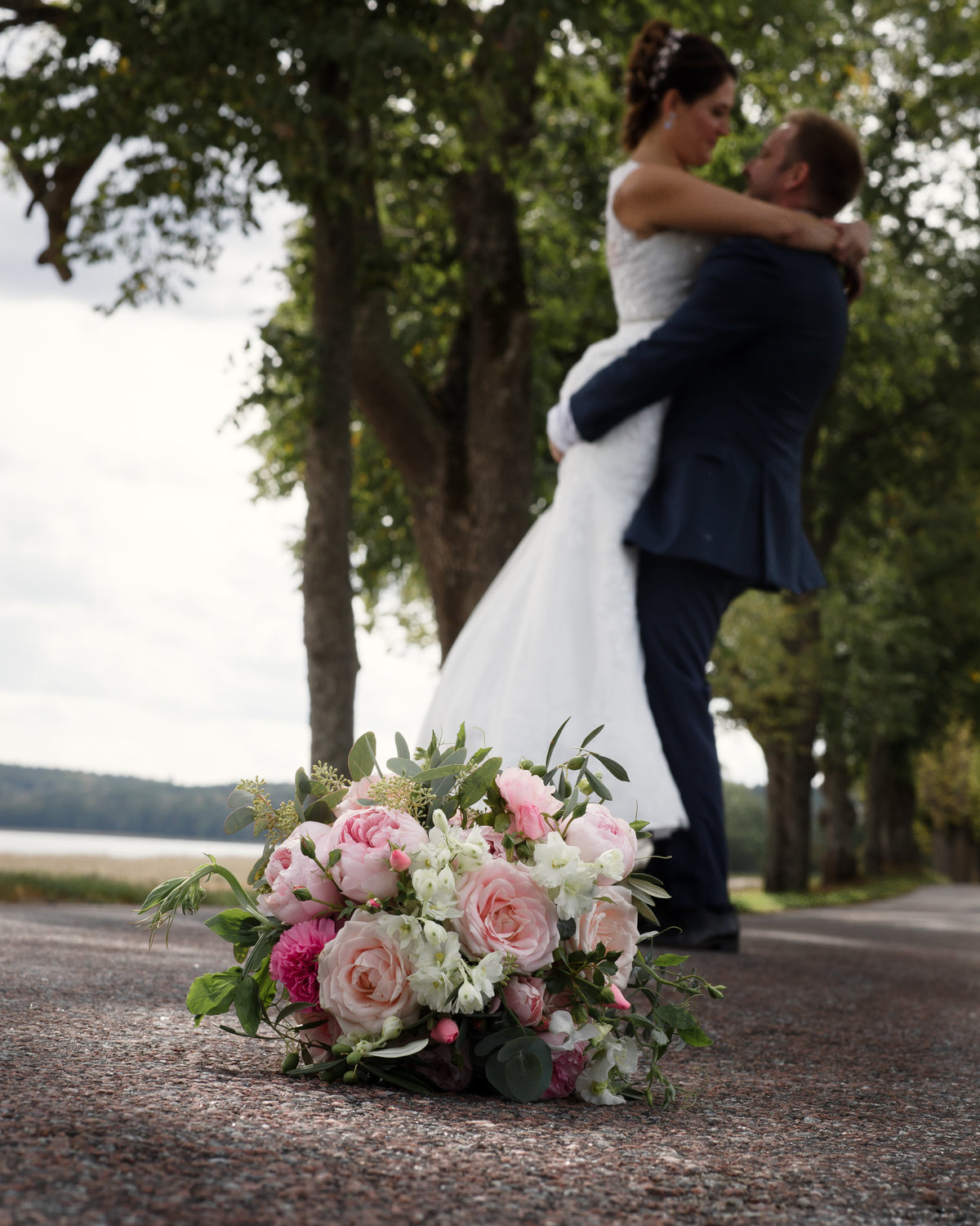 Groom lifts up his bride with the pink peony weddingbouquet in front of them in the alley