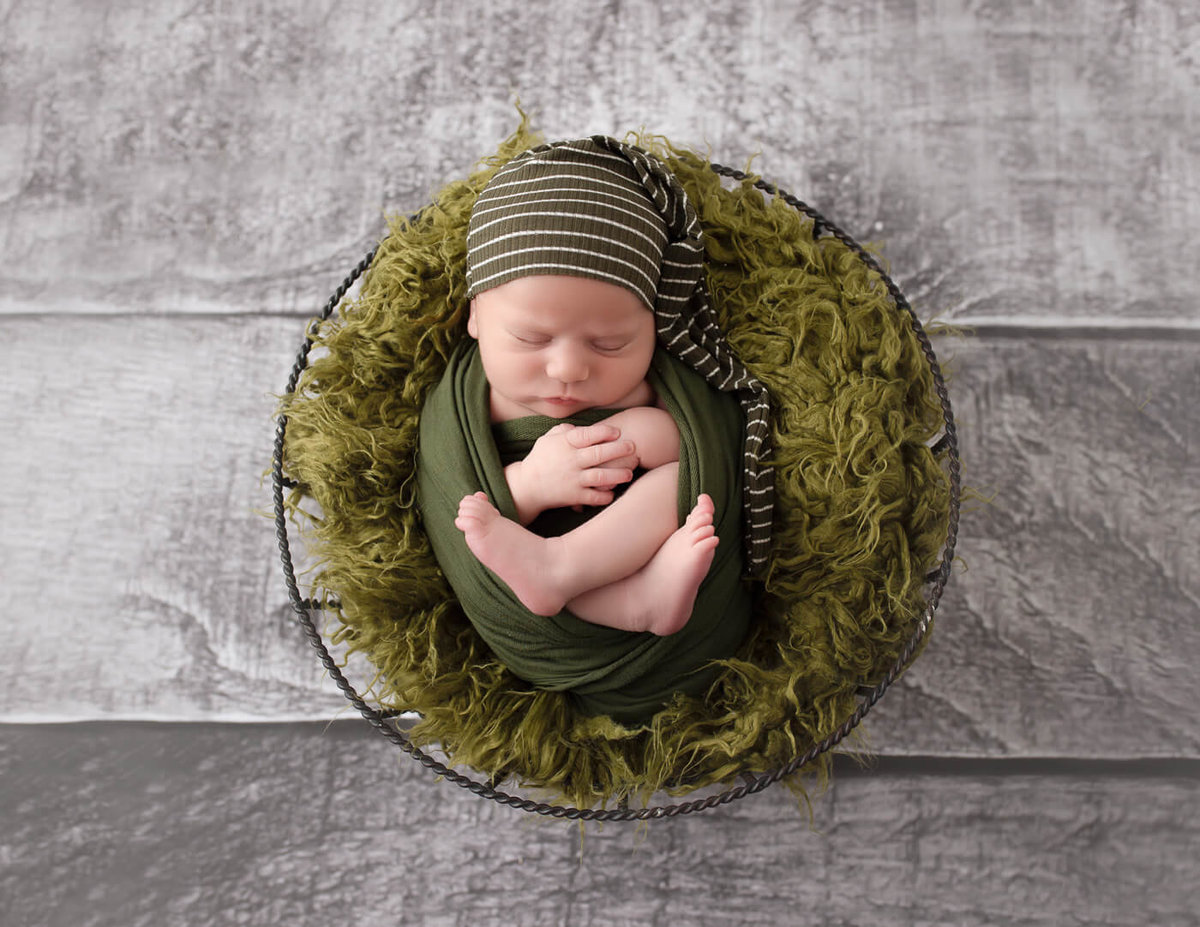 Newborn boy sleeping in a wire basket in our Rochester, NY studio.