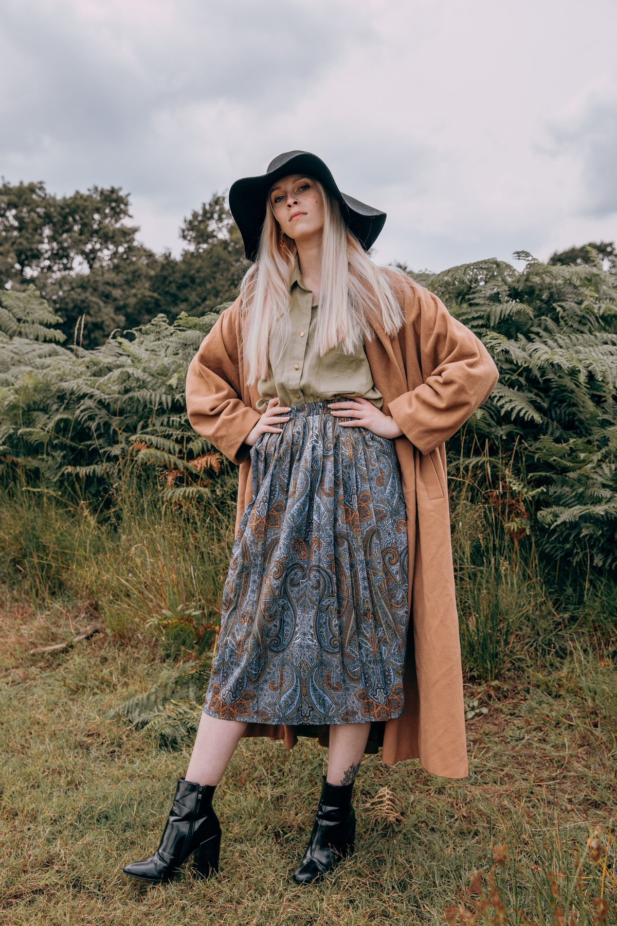 Amber wearing a long brown coat and a blue skirt against a backdrop of ferns in Richmond Park