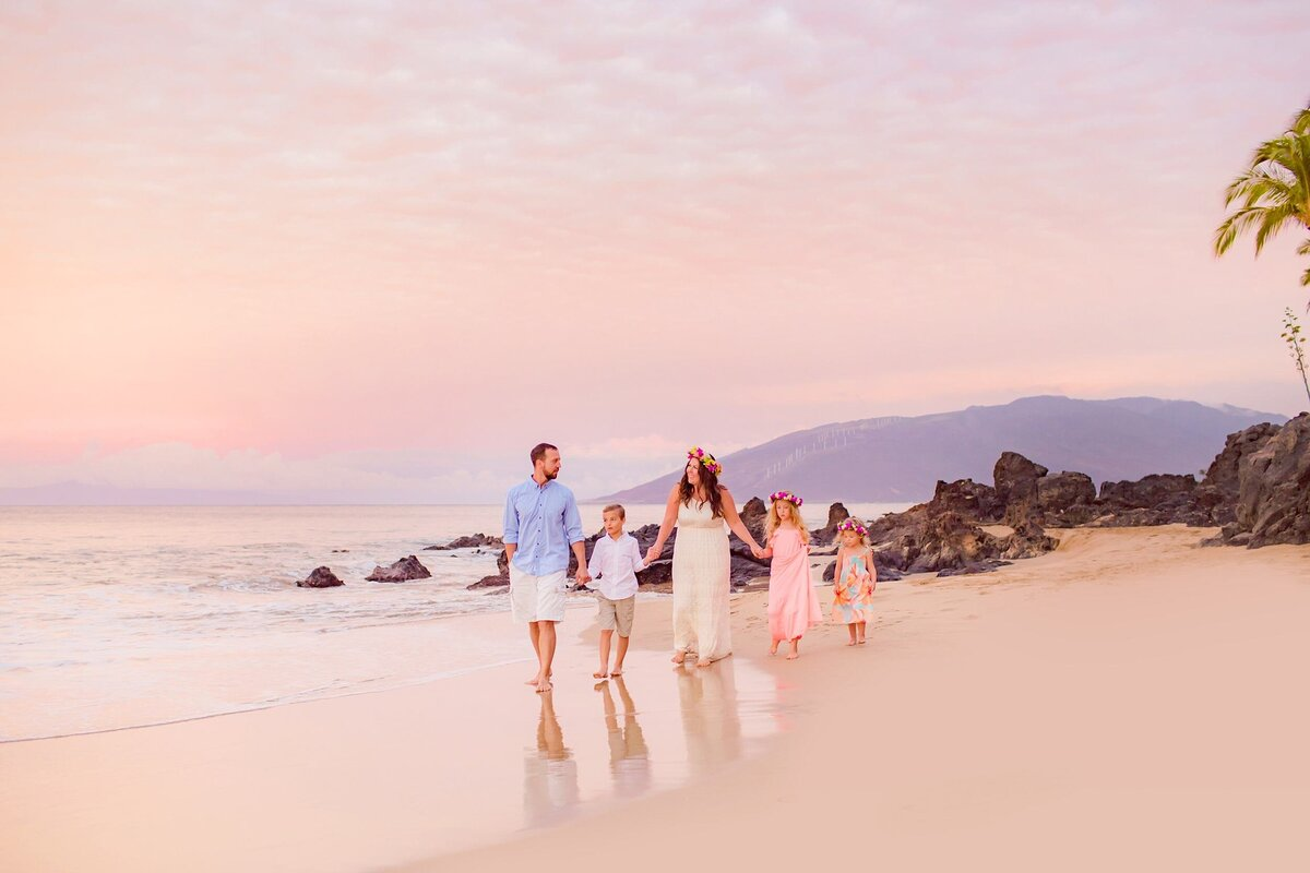 Family of five holds hands at the beach on Maui