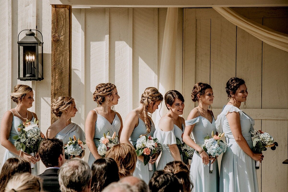 Bridal party wearing teal dresses wildflower bouquets smiling at bride
