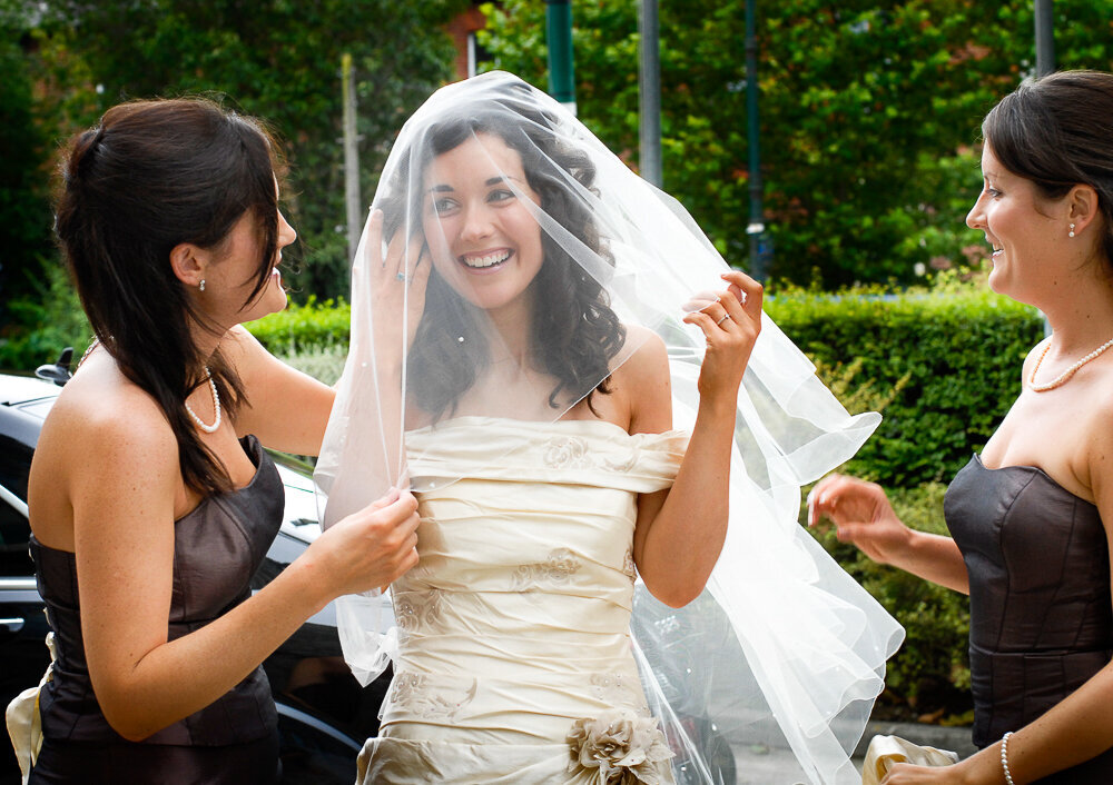 brunette bride wearing a veil over her face and balcony style wedding dress being helped by her bridesmaids wearing chocolate brown, sleeveless dresses
