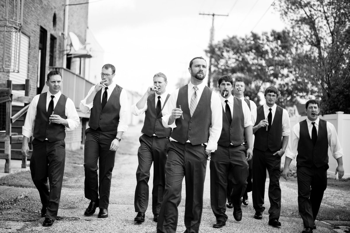 groomsmen walking and smoking cigars