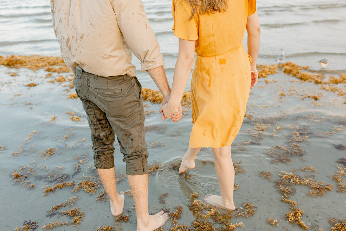 Engaged couple hold hands on a Florida beach during their engagement session