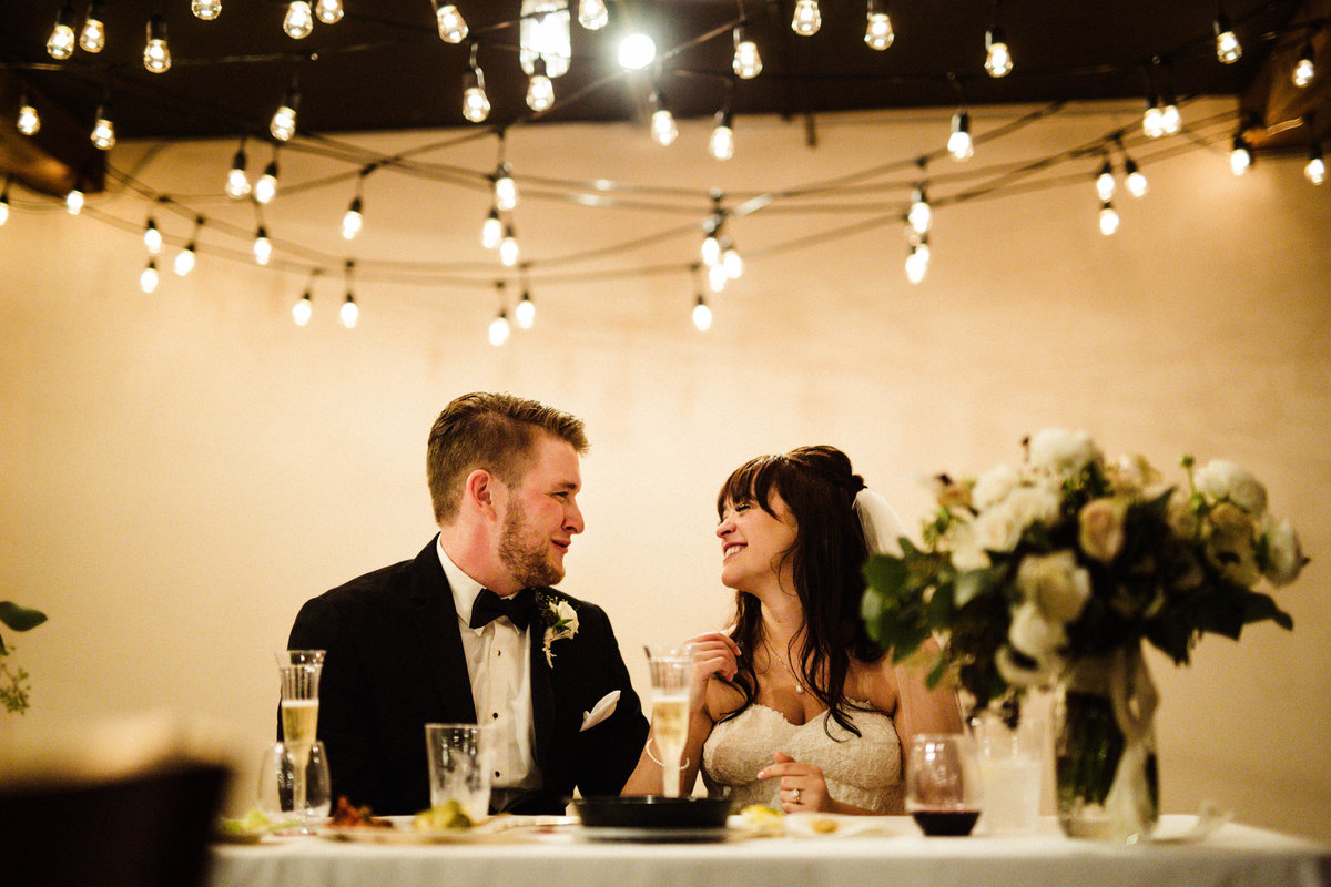 bride and groom smile at each other with twinkle lights overhead