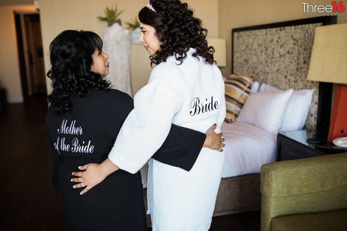 Bride posing with her mother in robes prior to getting dressed for the wedding