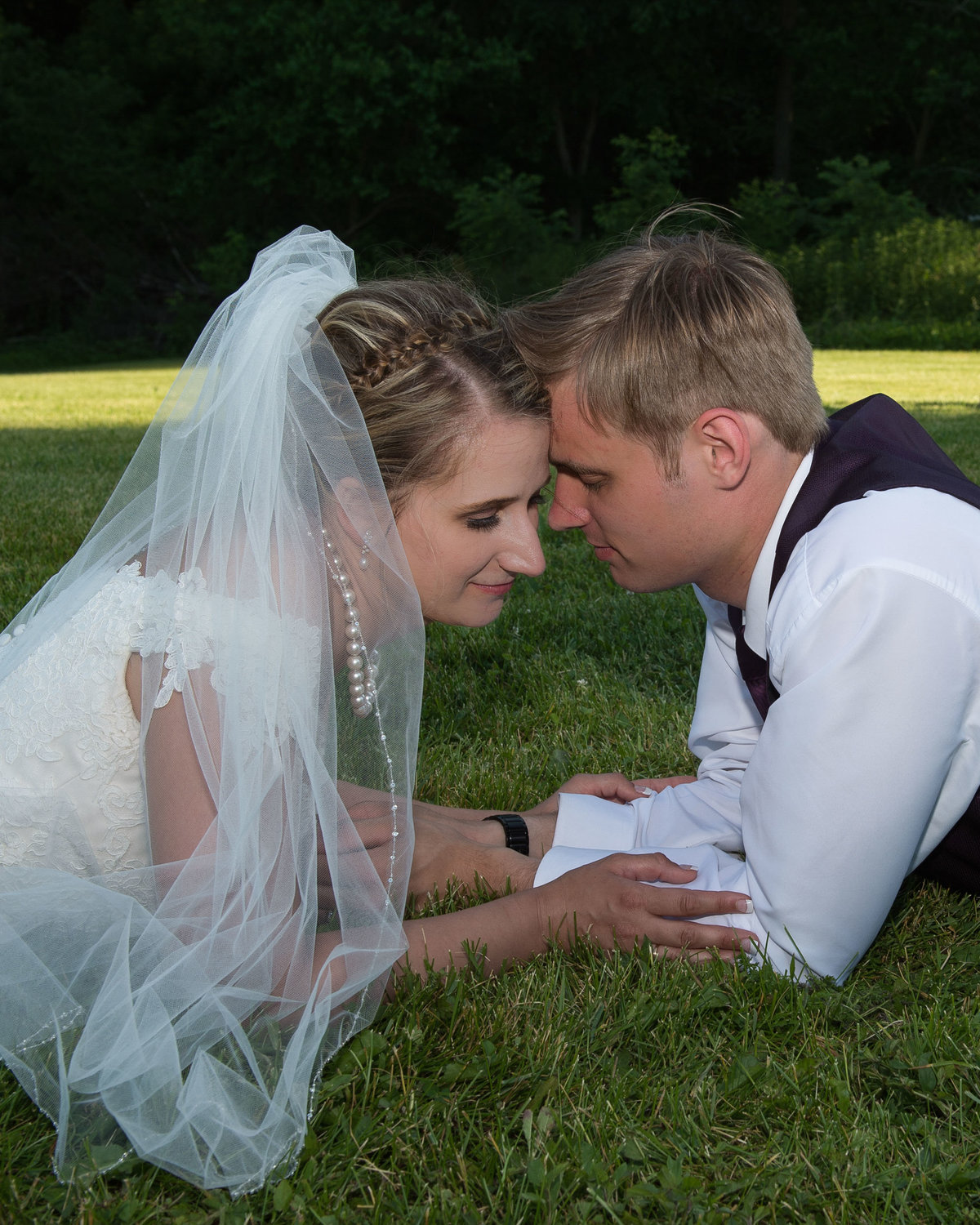 bride wears full beil and pearls posed in grass