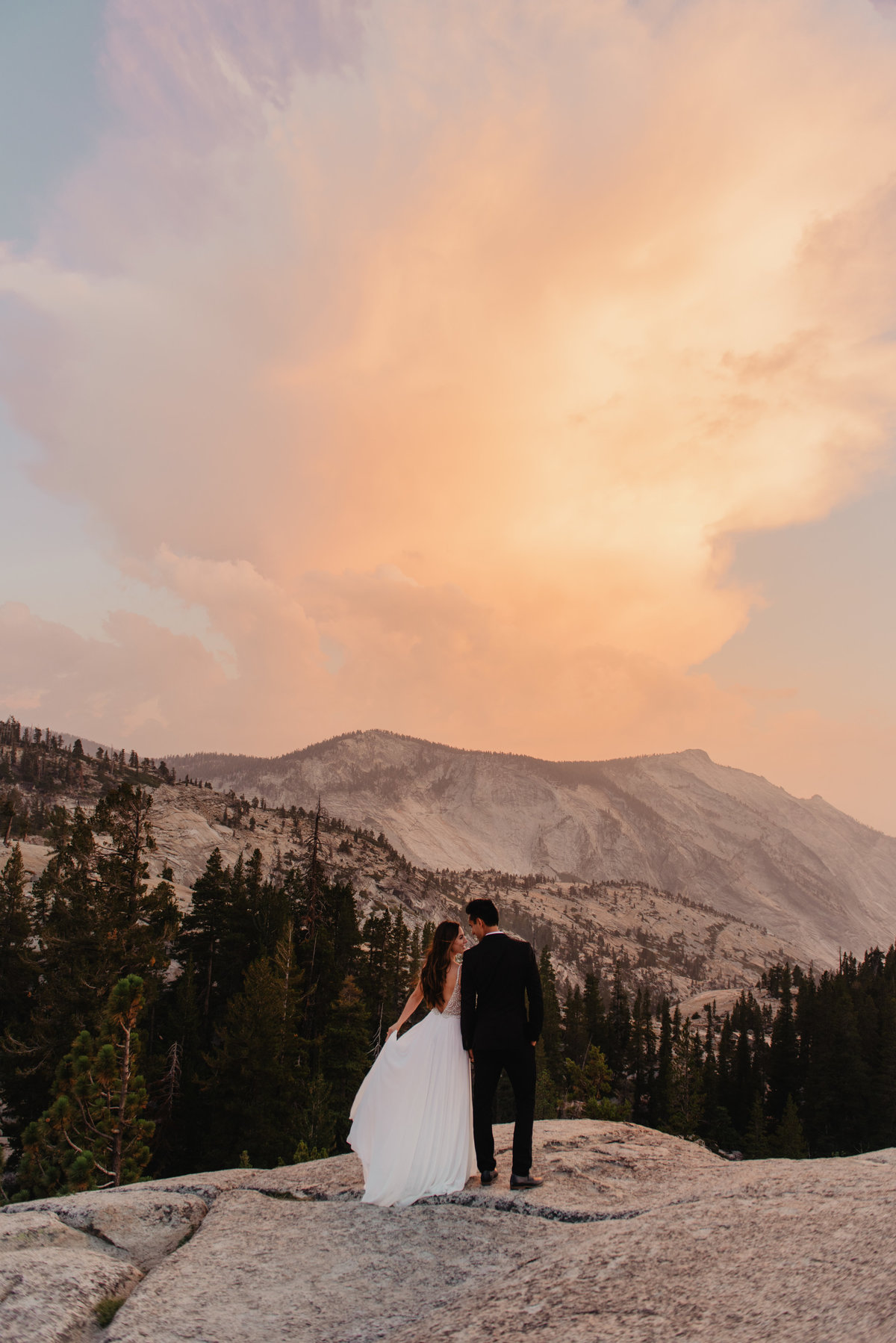 bride and groom in yosemite looking at a sunset