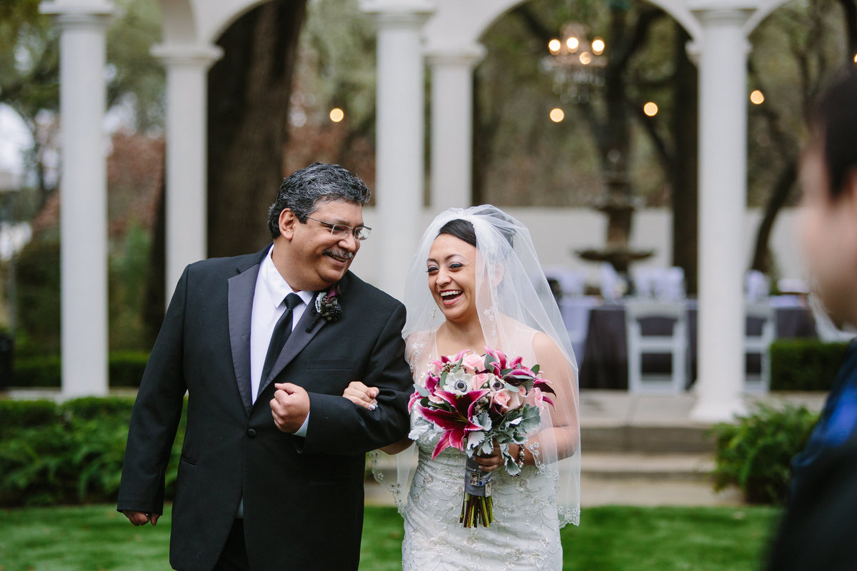 bride and father of bride laugh as walking down aisle during ceremony at Gardens at West Green Venue in San Antonio
