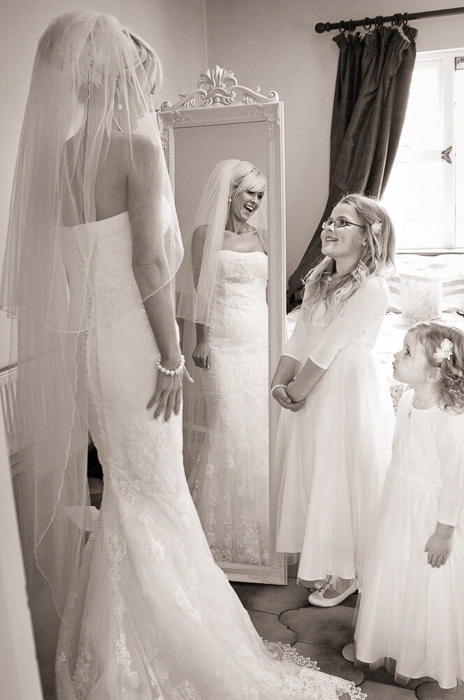 bride with blonde hair wearing veil and trumpet style, sleeveless, lace wedding dress, in front of mirror, smiling at her flowergirls