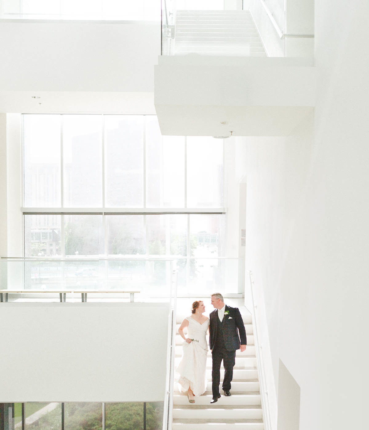 bride and groom descend stairs of rochester art center minnesota