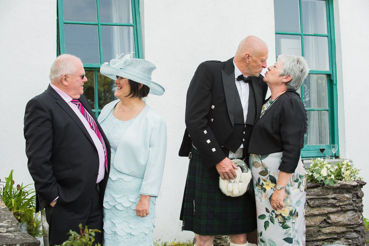 two couples at a wedding sharing a tender moment at Castlecove House