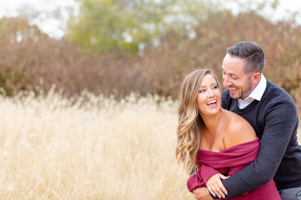Fall Sunset Engagement  Session with pink off the shoulder dress couple laughing  by tall grass at Pagoda Circle  in Forest Park in St. Louis by Amy Britton Photography Photographer in St. Louis
