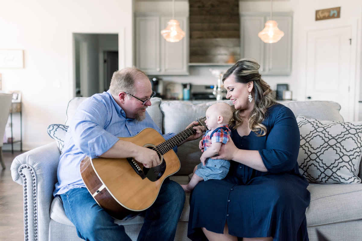 Father is playing guitar to newborn son and mother is holding newborn son and singing as dad plays guitar