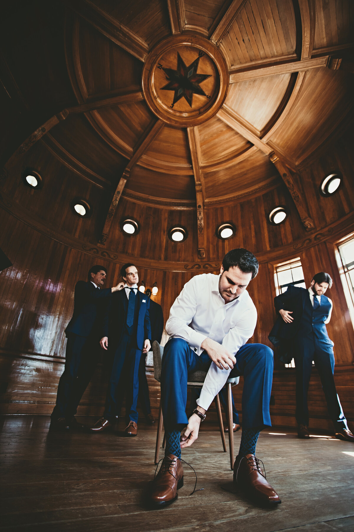 A picture of the groom and two groomsmen getting dressed for the wedding ceremony in a handsome round room with wooden walls and ceiling at the ceremony venue by Garry & Stacy Photography Co - Tampa FL wedding photographer