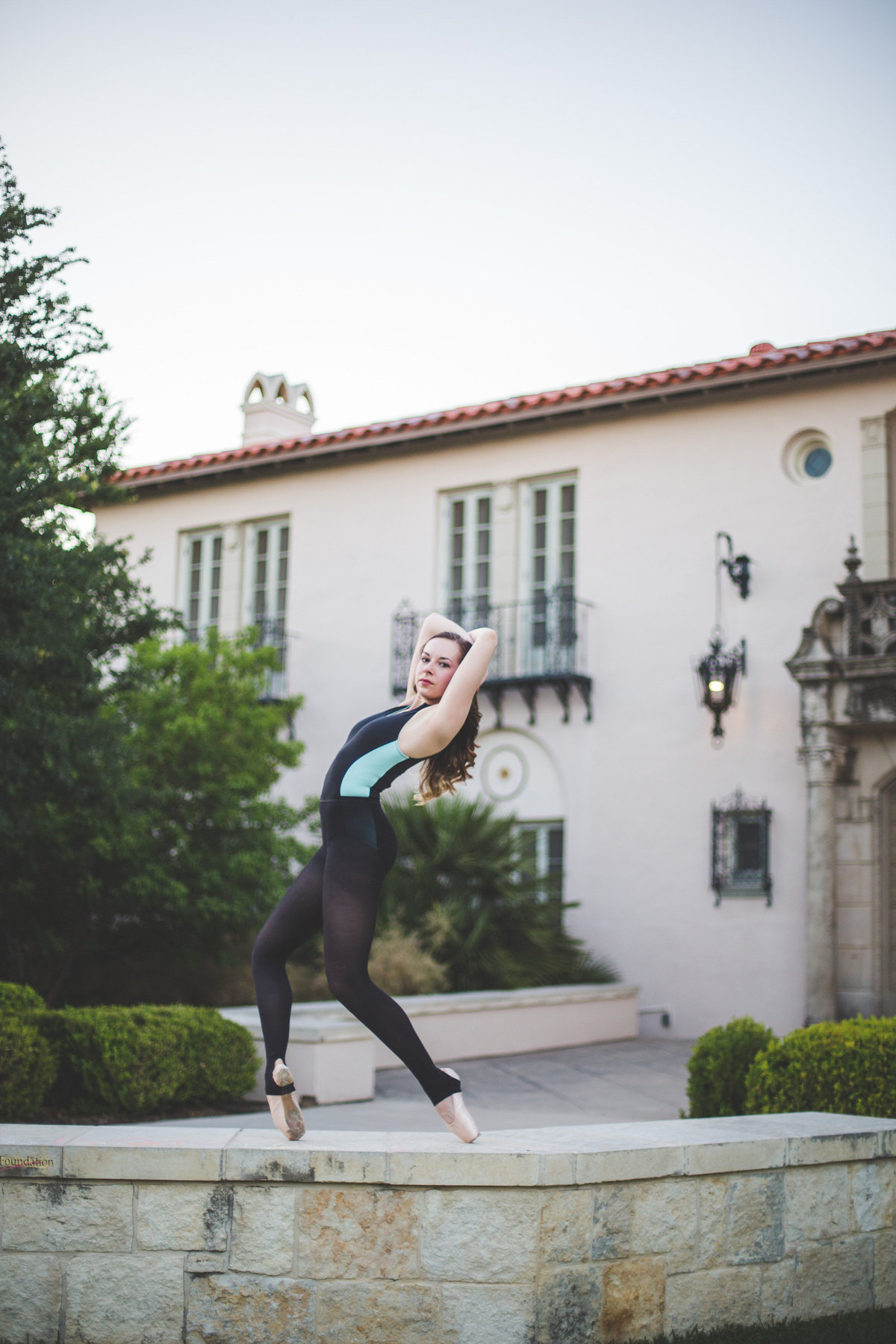 senior girl high school ballerina posing and bending back by San Antonio senior photographer