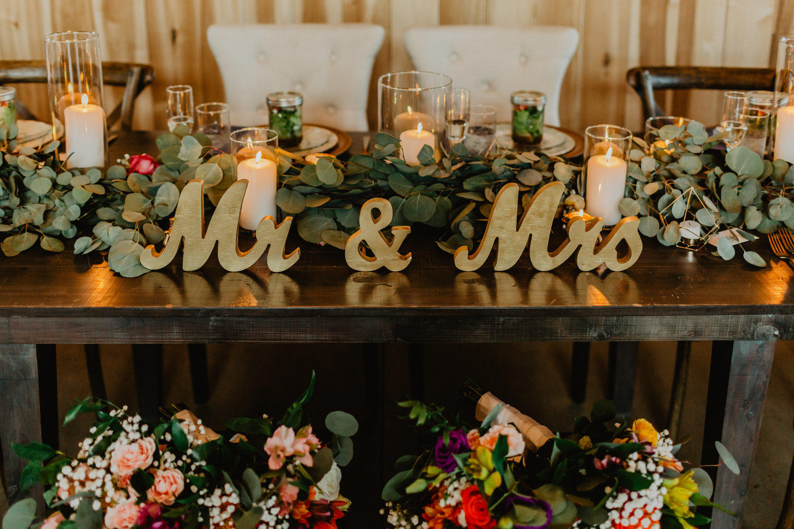 Bride and Groom table featuring Mr and Mrs signs and lush green florals at Allenbrooke Farm