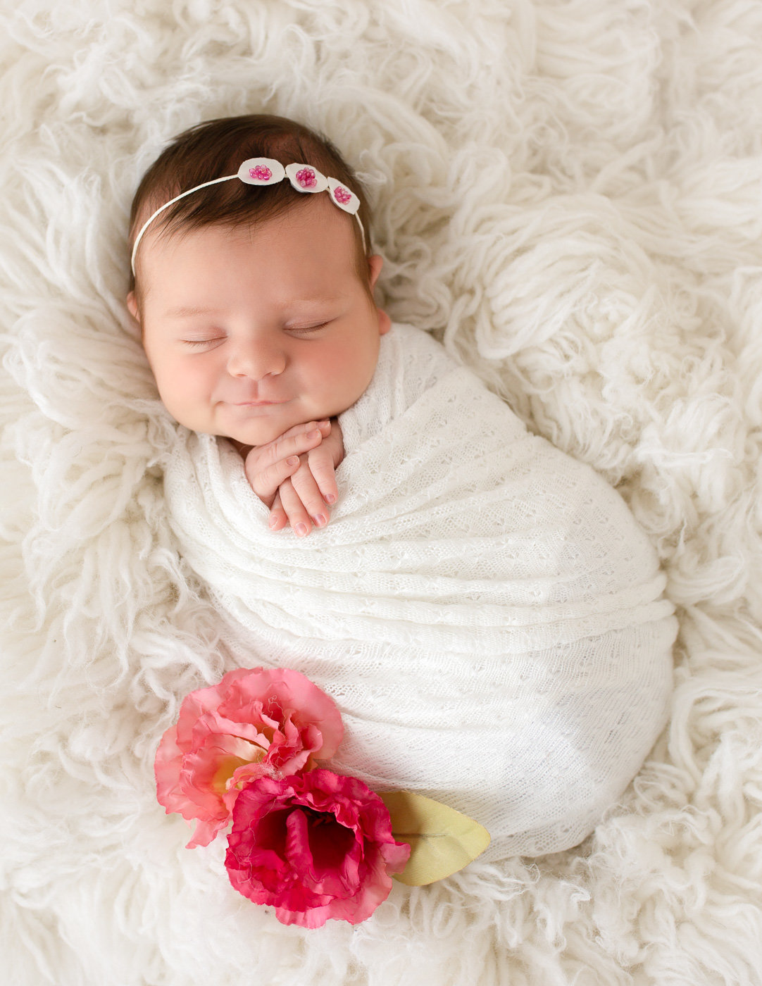 Sweet smiley newborn girn posed in our Rochester, NY studio.