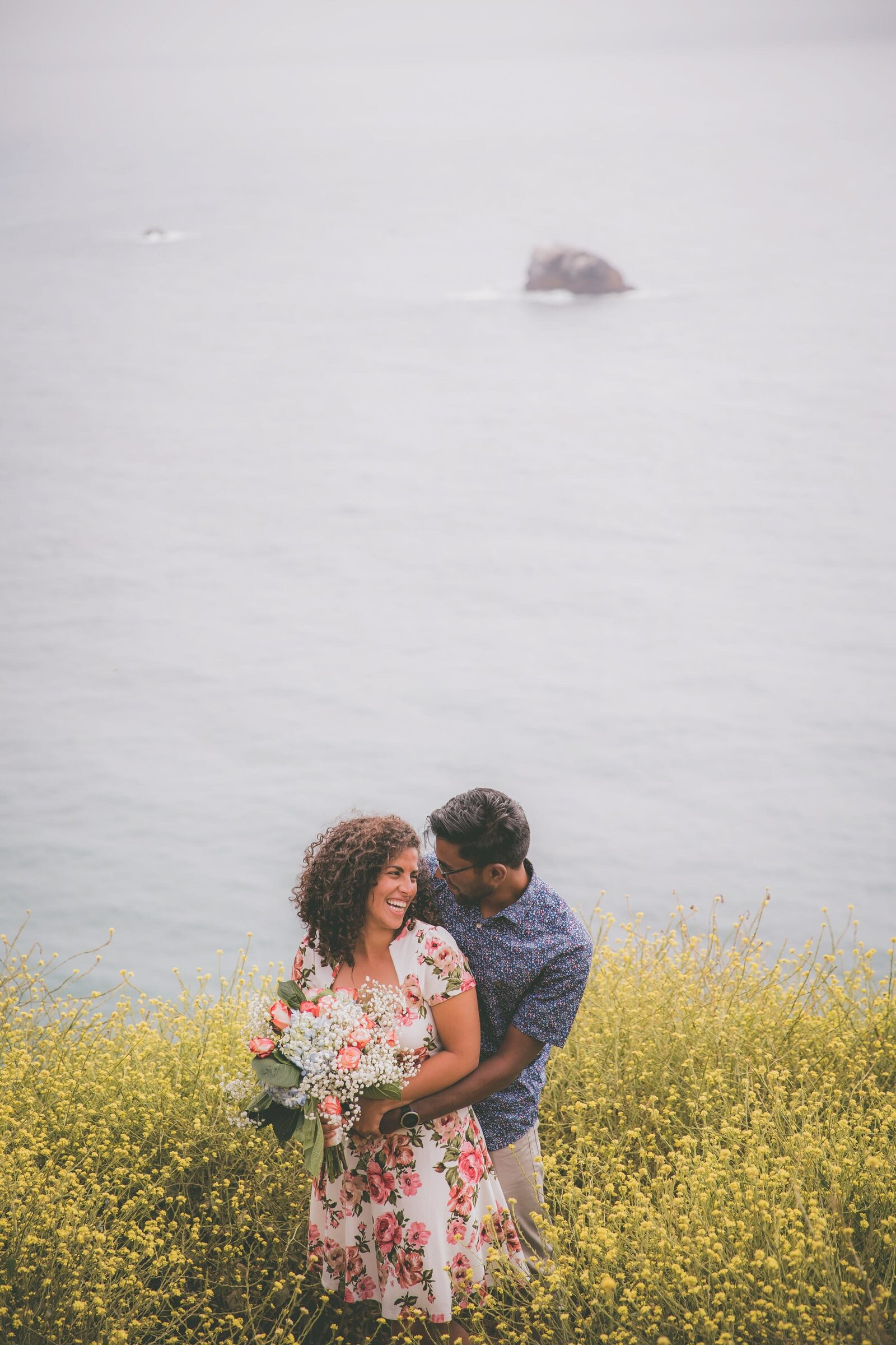 Couple goes in prom pose among yellow wildflowers in Big Sur.