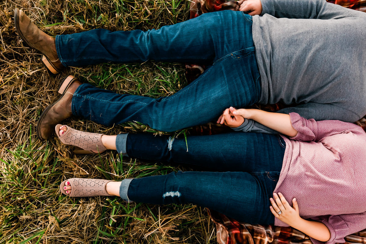 Kansas City engagement photo of a couple lying in the grass holding hands