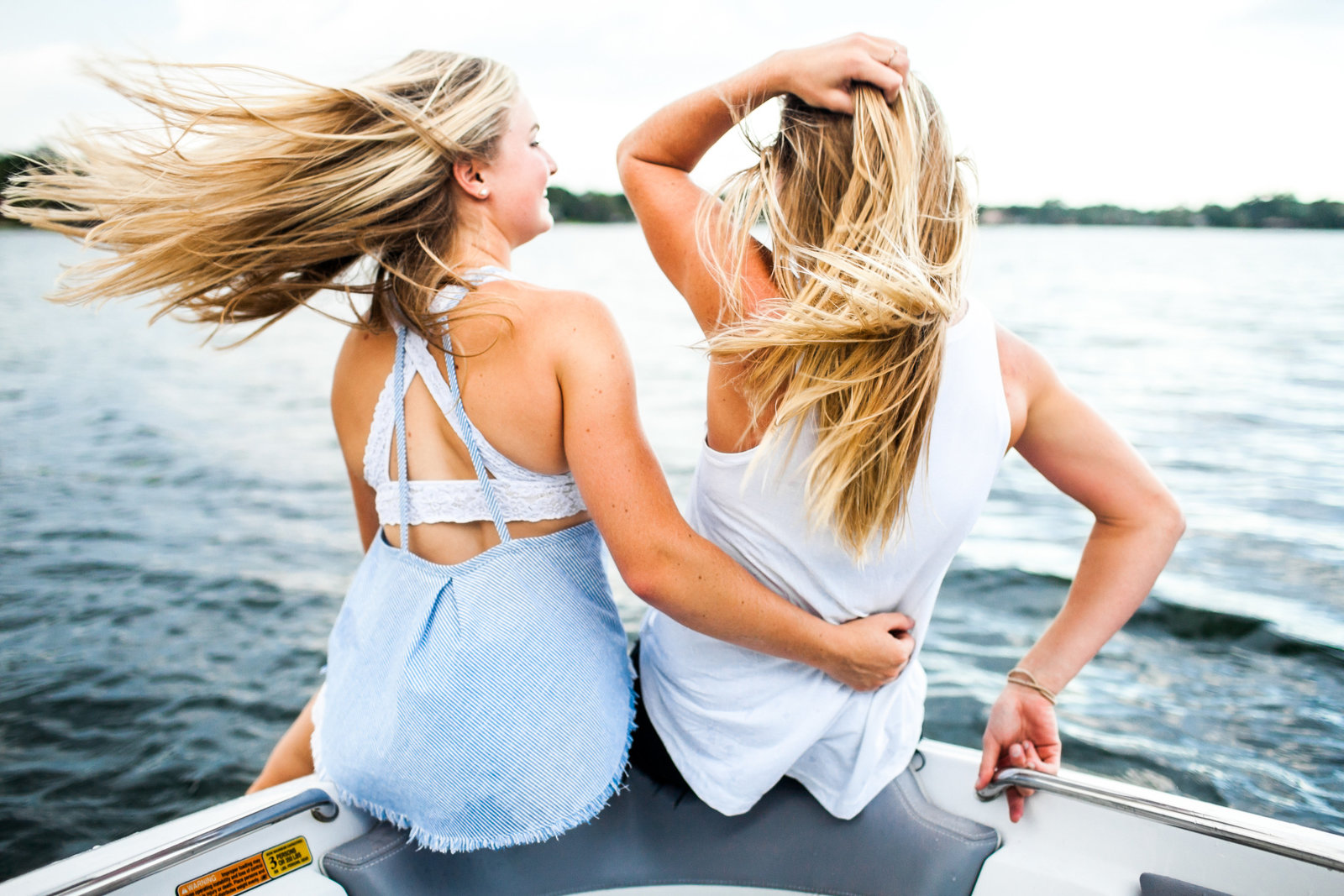 Best friends on a boat with hair blowing in the wind