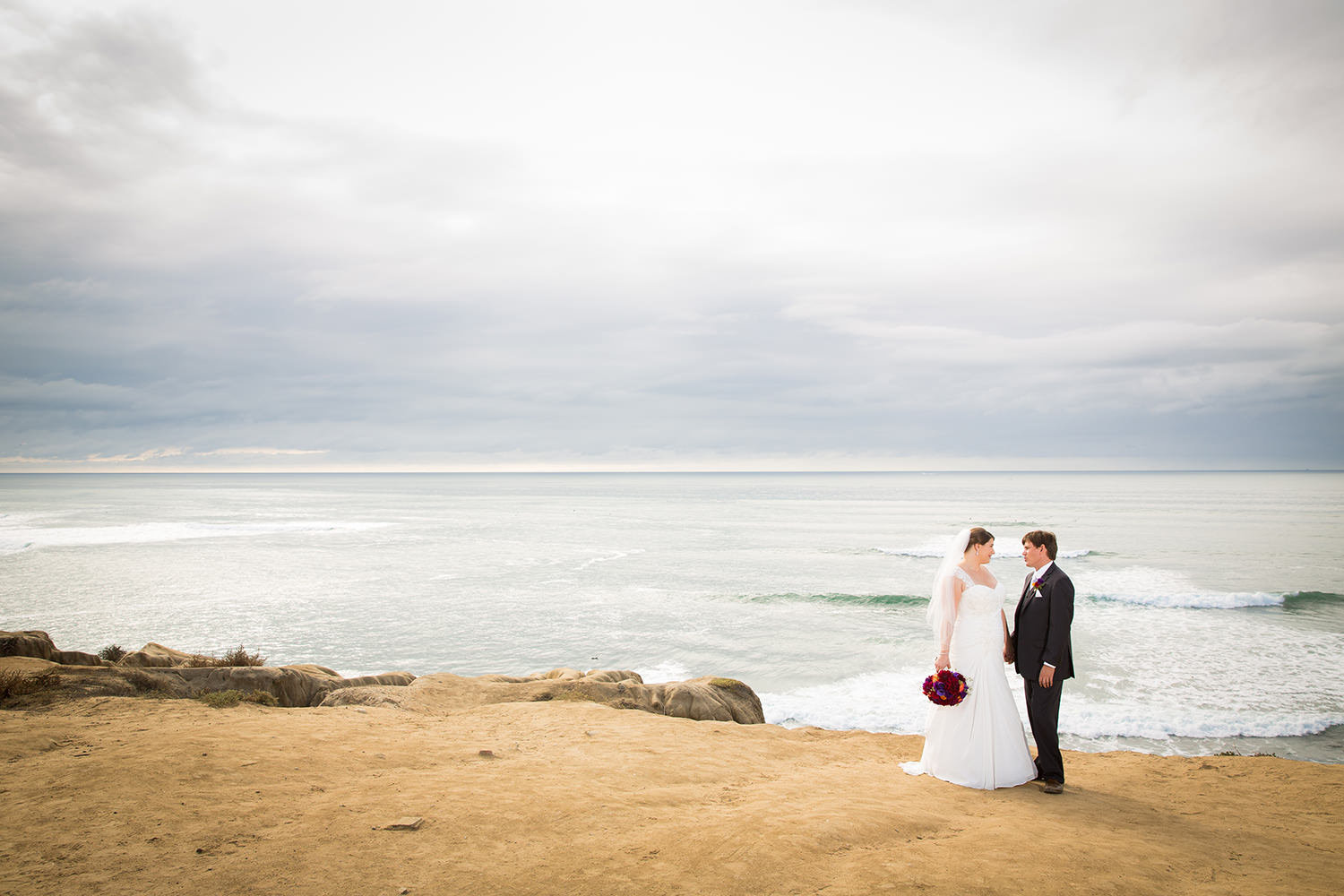 bride and groom with ocean in back ground
