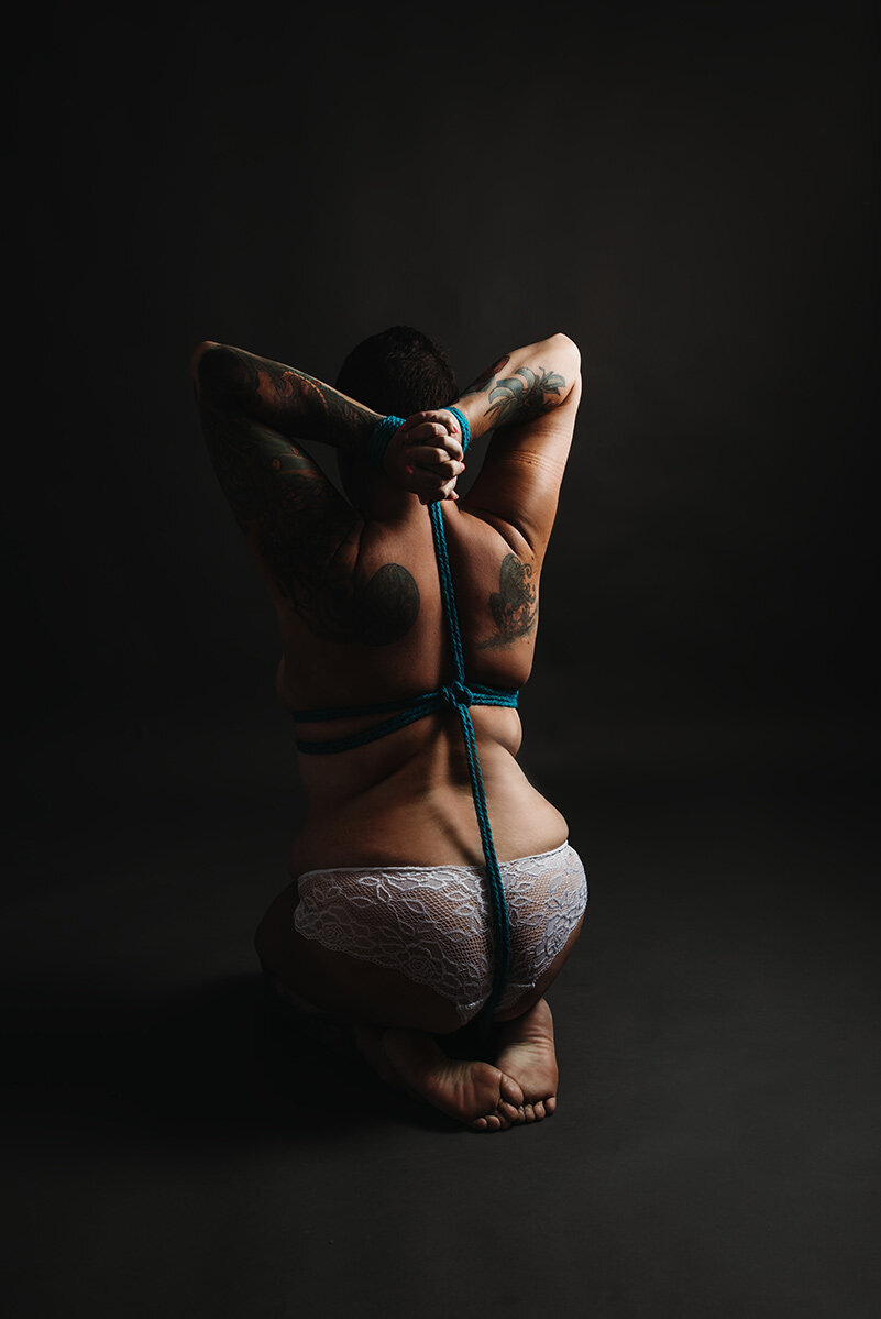 Woman kneeling upright with teal ropes