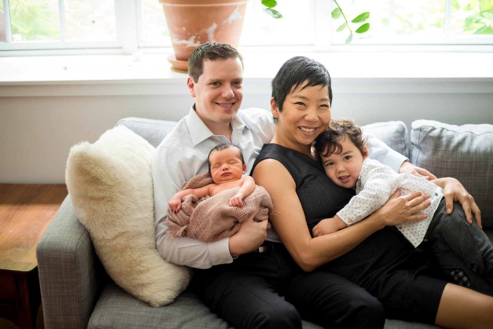 parents hugging newborn at home lifestyle session family photo