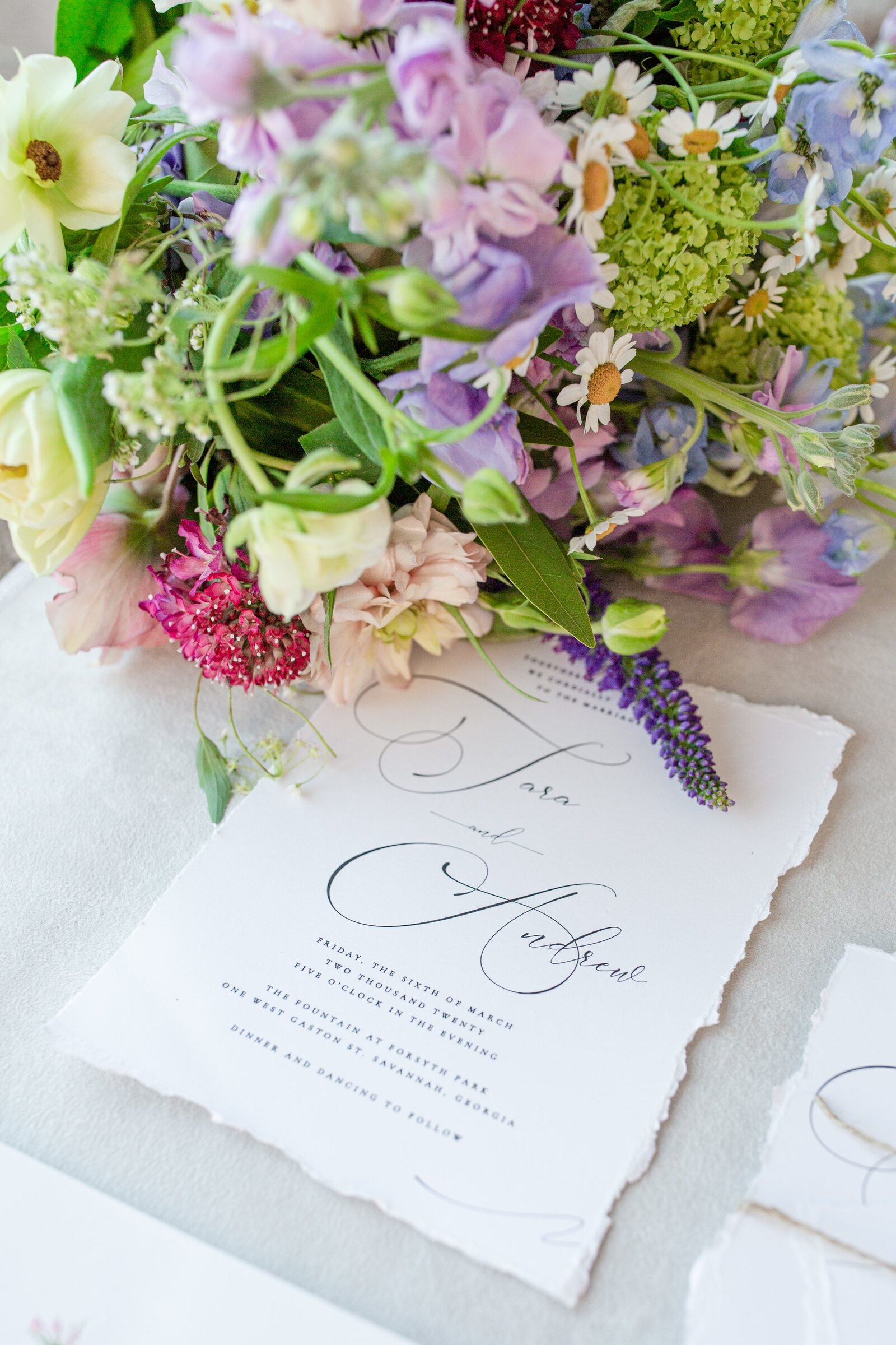 detail photo of a wedding invitation and a spring wildflower bouquet