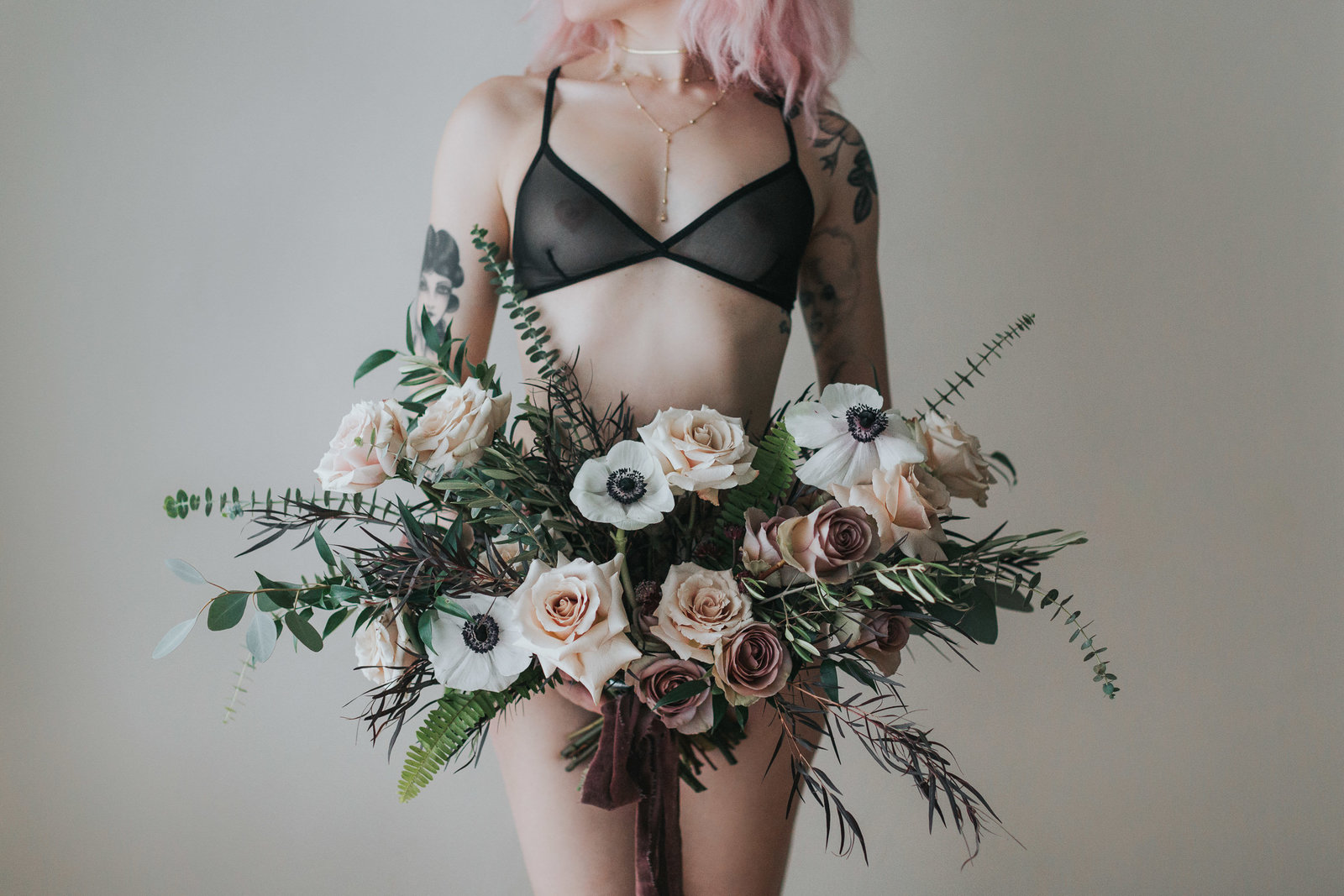 Girl in lingerie holding bouquet of flowers