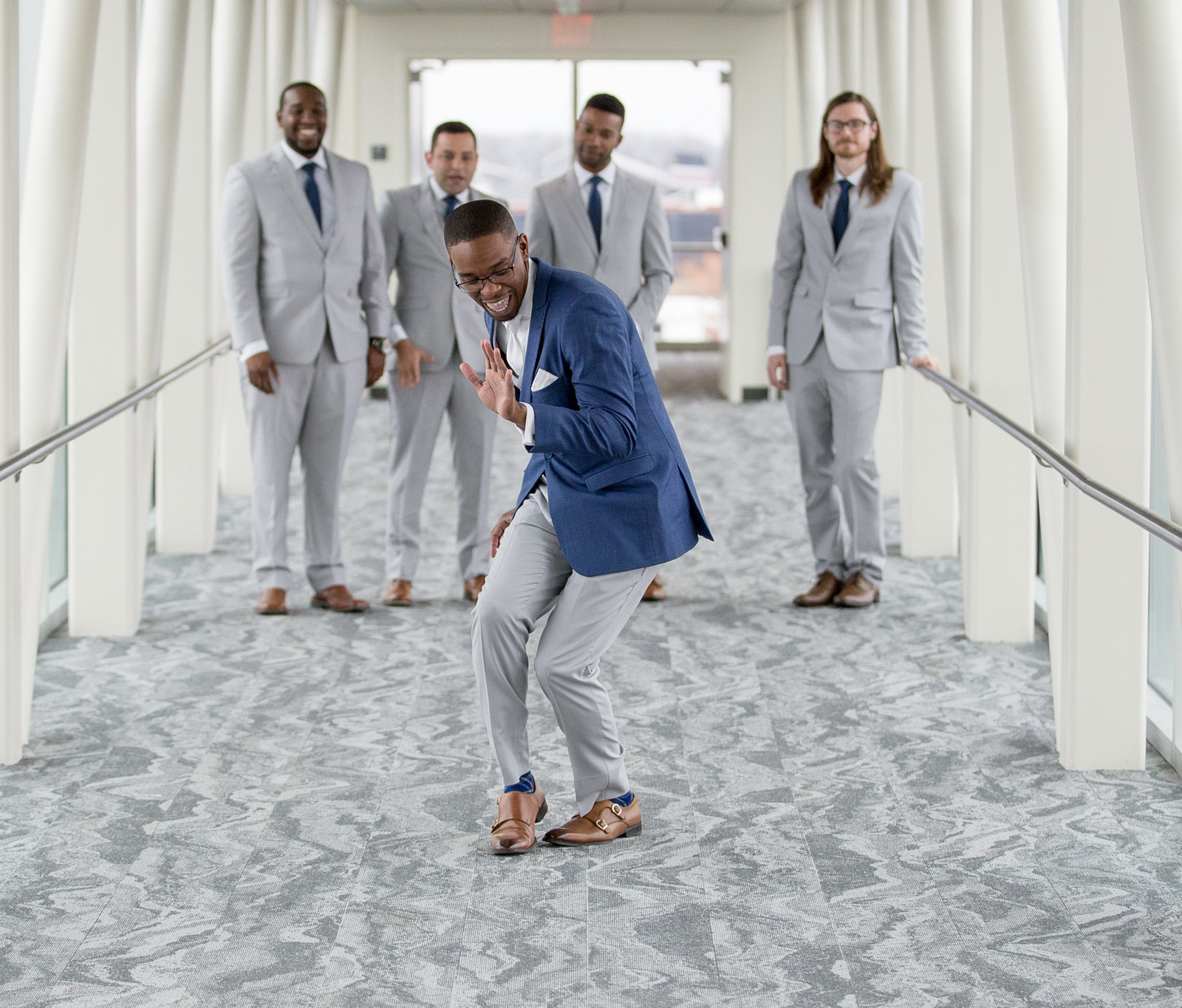 Groom dances down the skybridge at Sheraton Erie Bayfront Hotel while his groomsmen look on