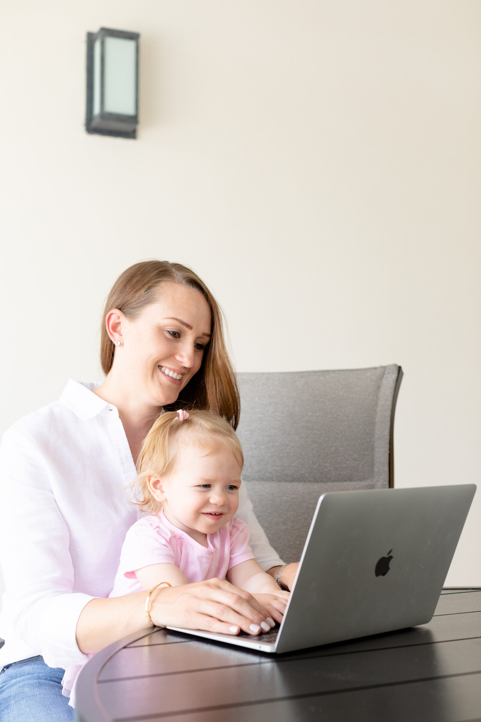 mom sitting with her daughter at the laptop