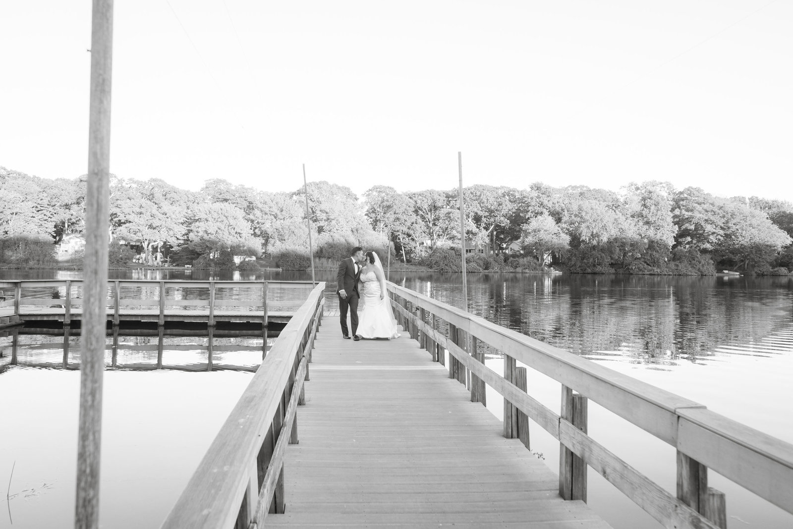 Bride and groom walking down dock at Camp Pa-Qua-Tuck