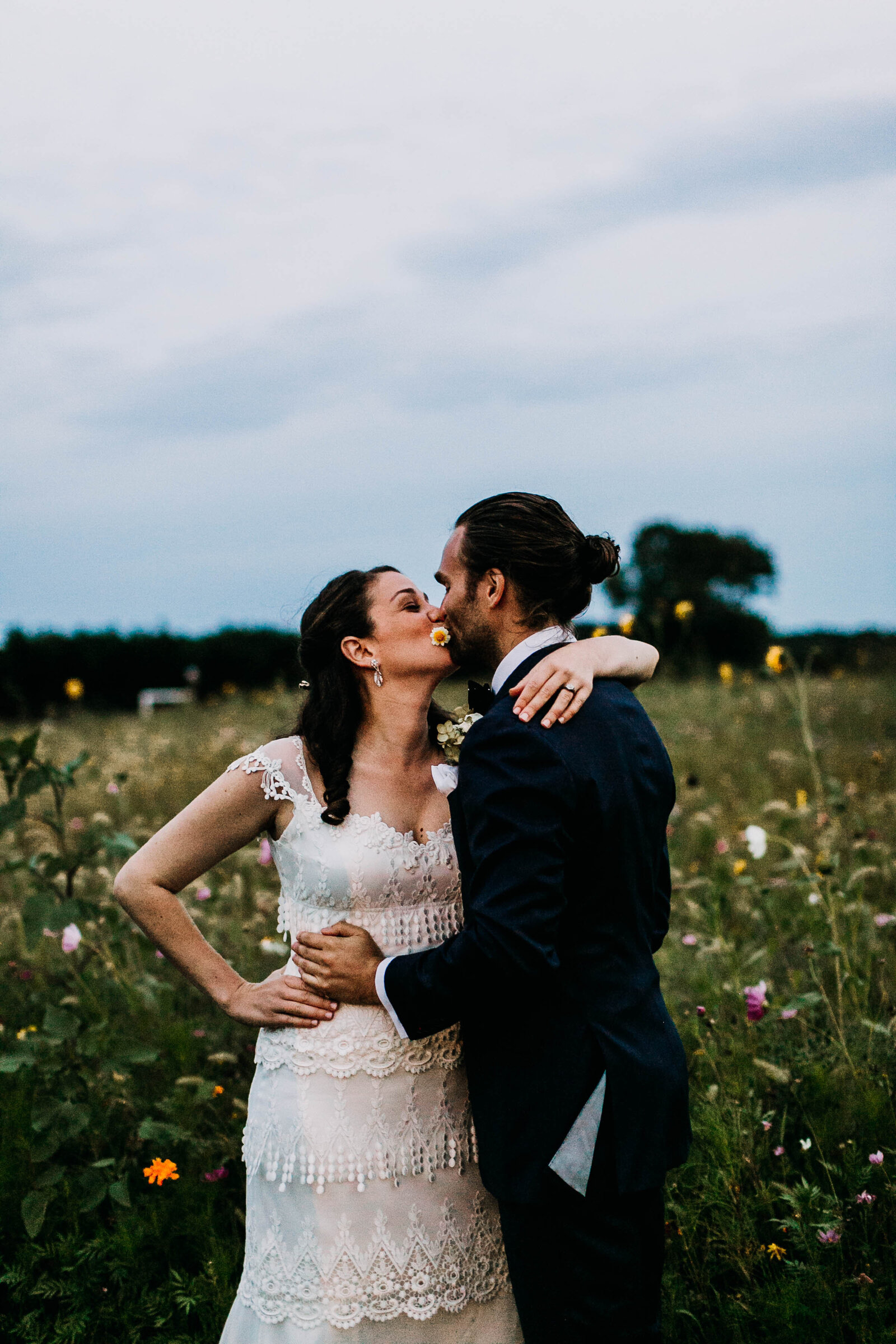 bride and groom kissing in flower field