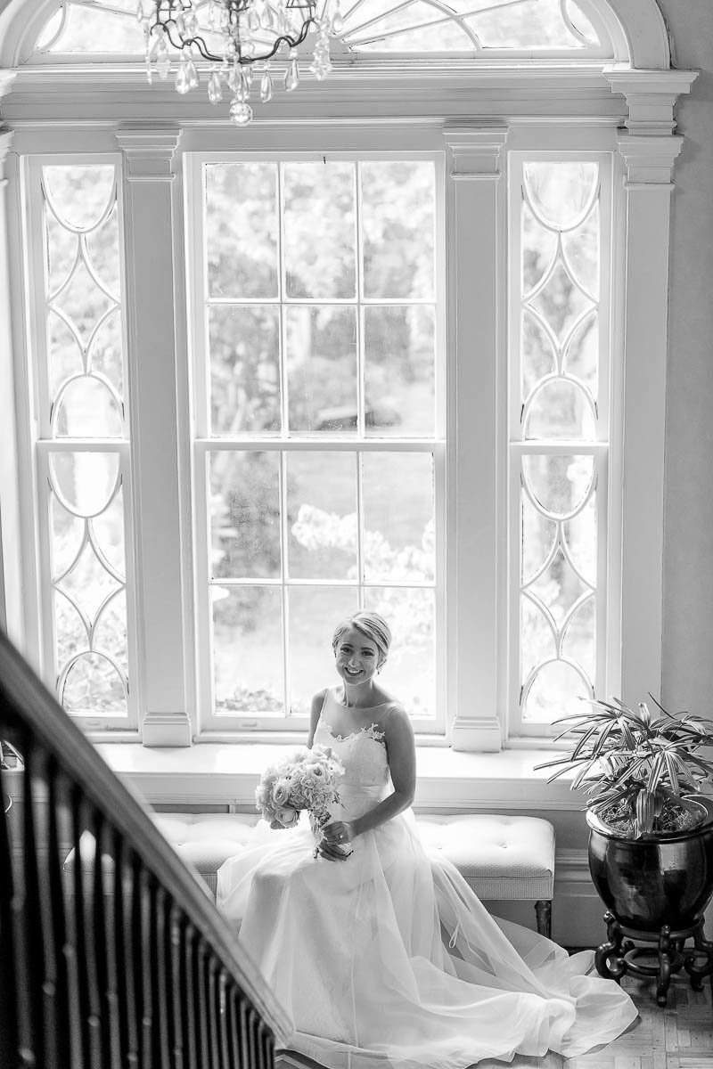 Bride sits in front of window, John Rutledge House Inn, Charleston, South Carolina