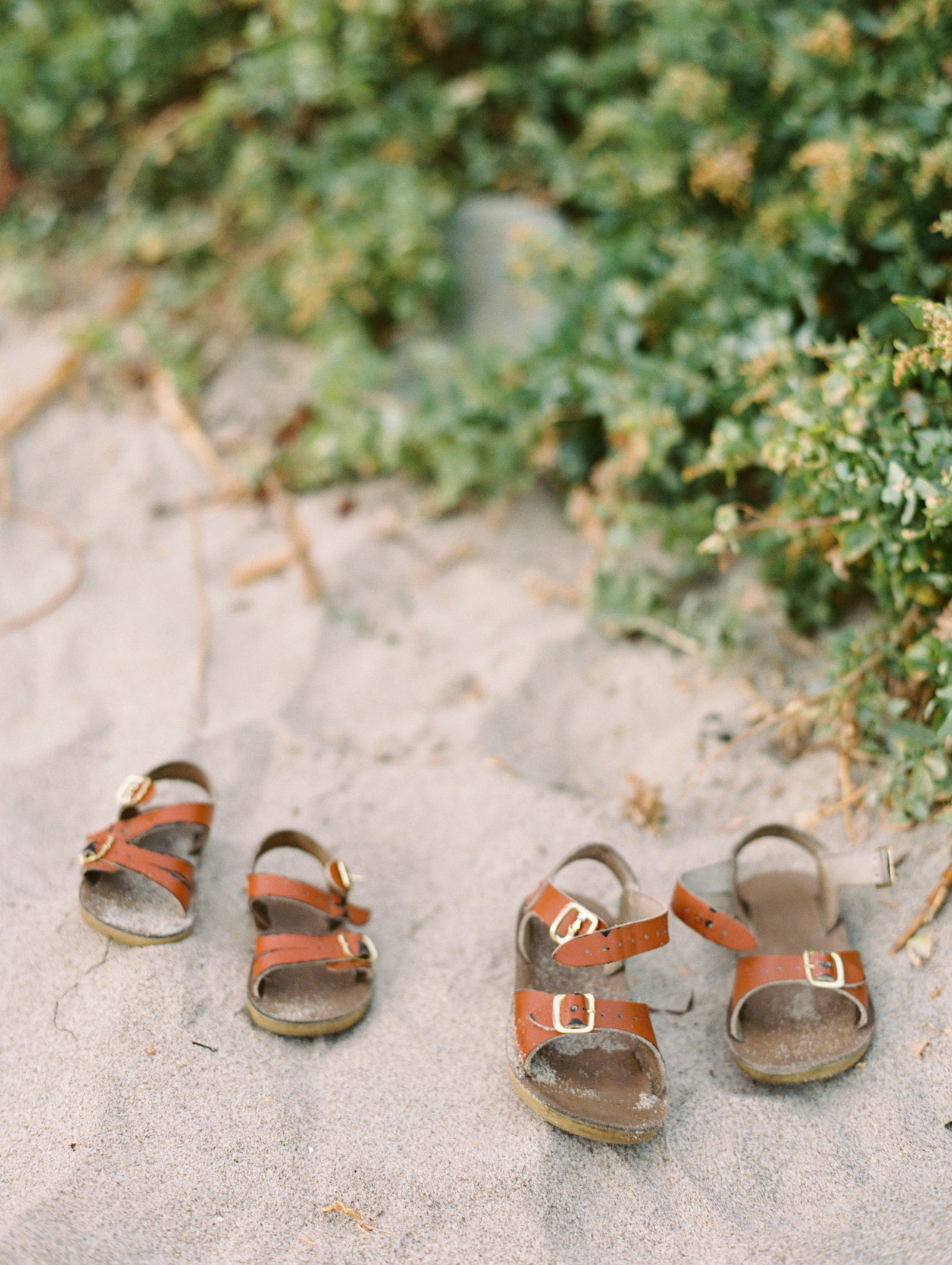 two pairs of little, brown saltwater sandals on the sand at the beach
