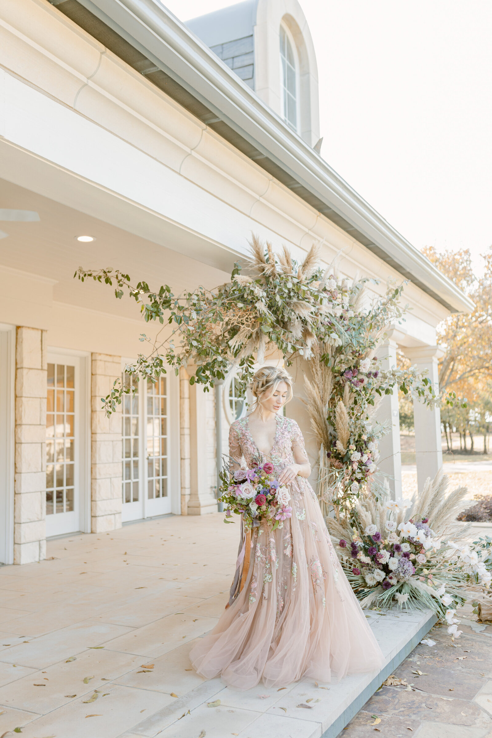 Beautiful bride outside of chateau underneath floral installation and holding a bouquet