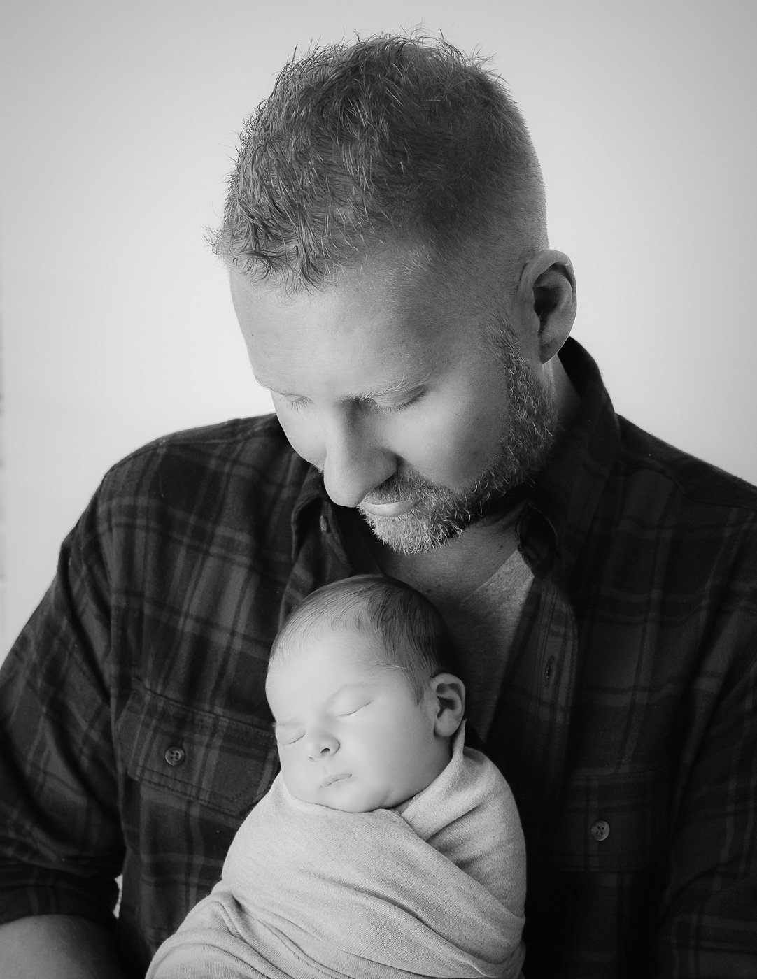 Father holding newborn son in our Rochester, NY studio.