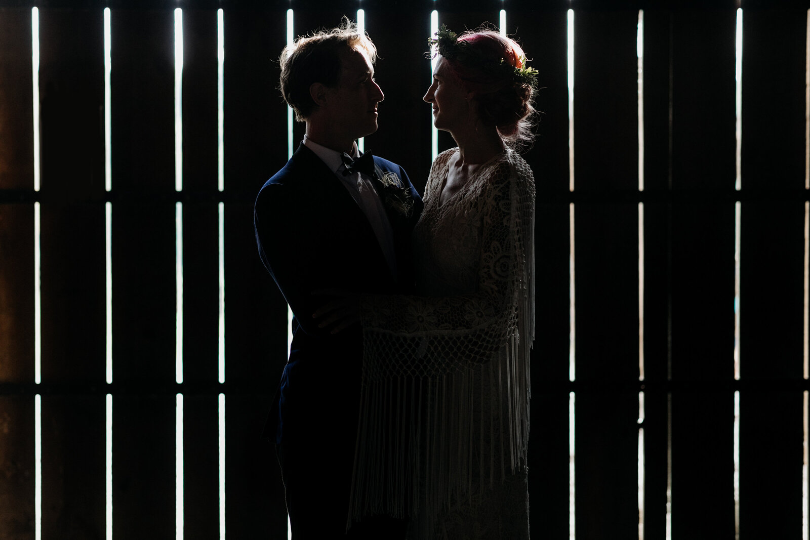 bride and groom in moody barn light