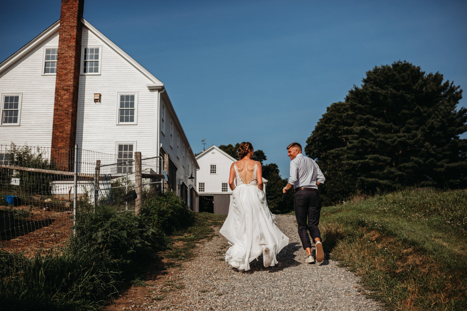 bride and groom hold hands and run past white barn