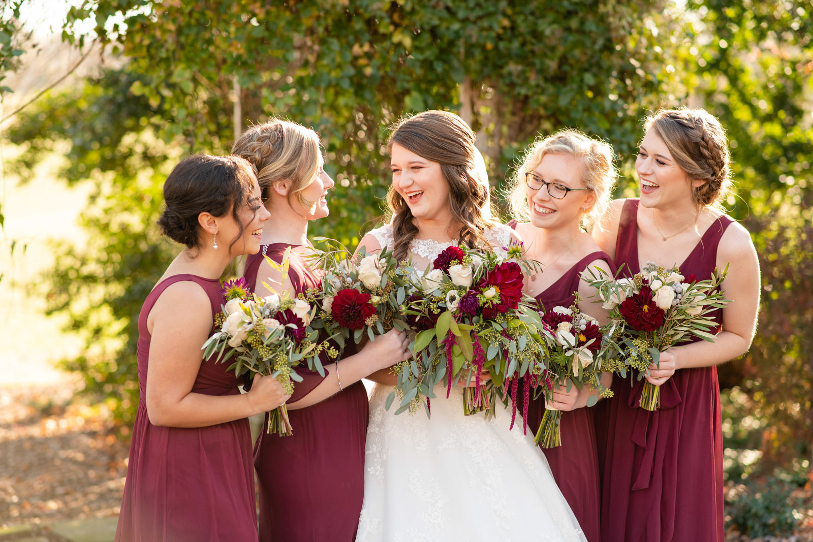 bride laughing with bridesmaids in burgundy dresses winter wedding