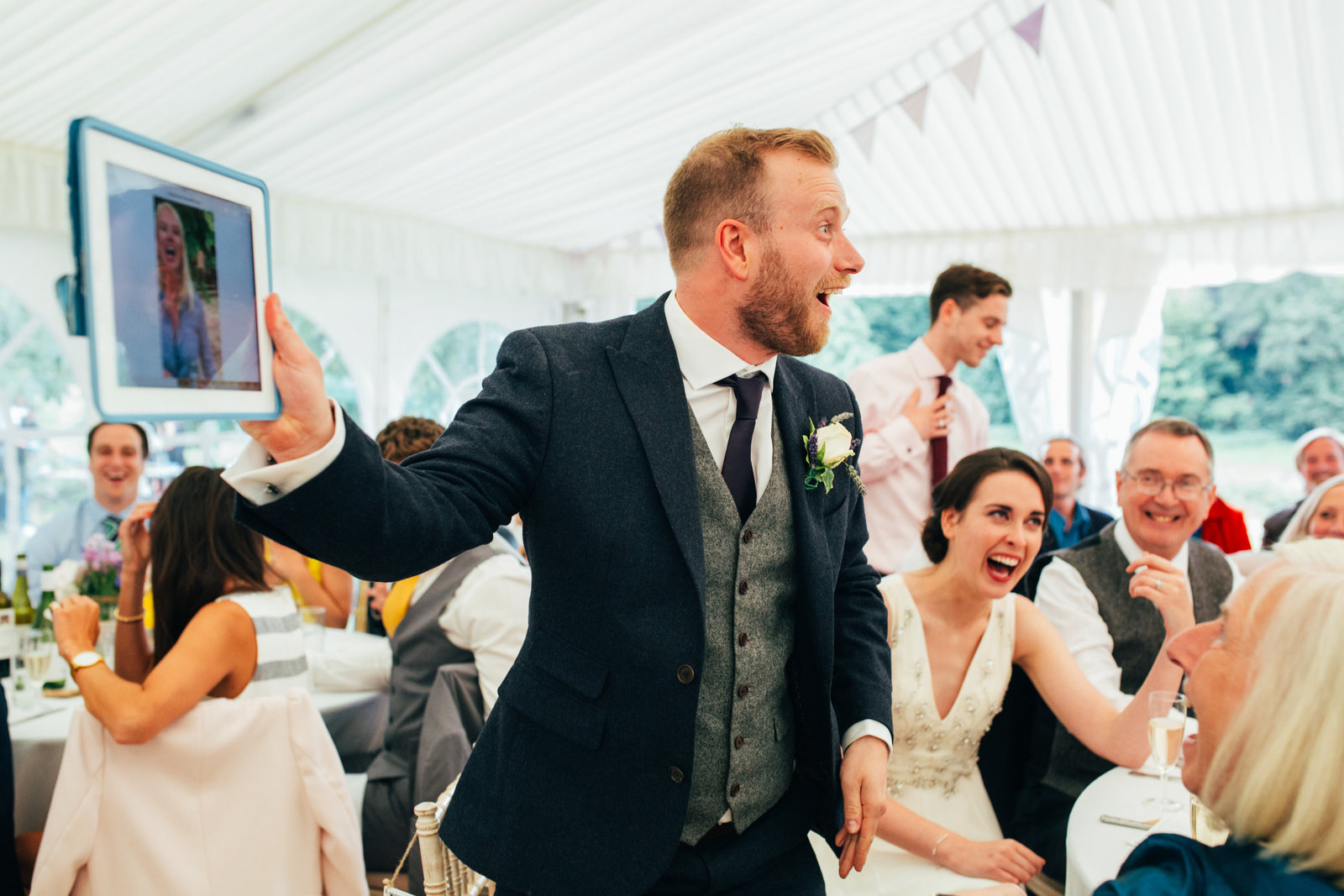 Groom laughing and animated during his speech surrounded by wedding guests in a white marquee