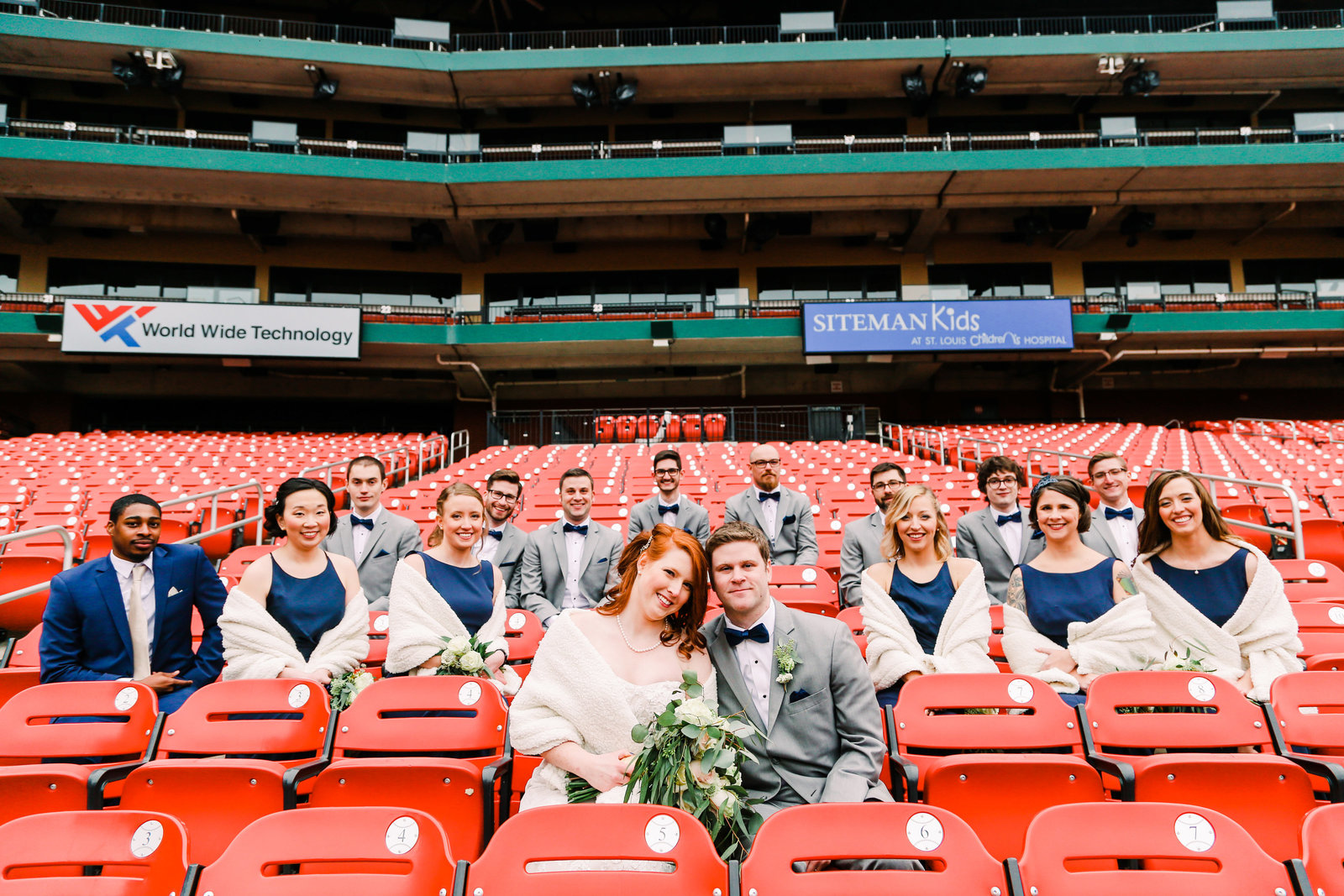 This wedding party ground together in the red seats of Busch Stadium with Bride and Groom in the row in front of them.