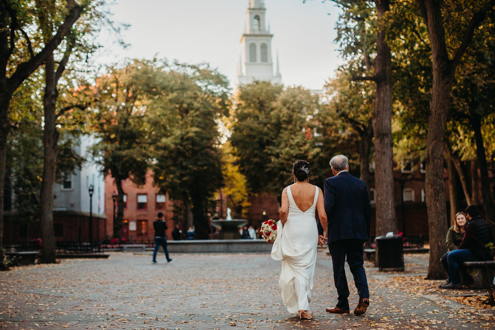 bride and groom walk through boston towards old north church during elopement