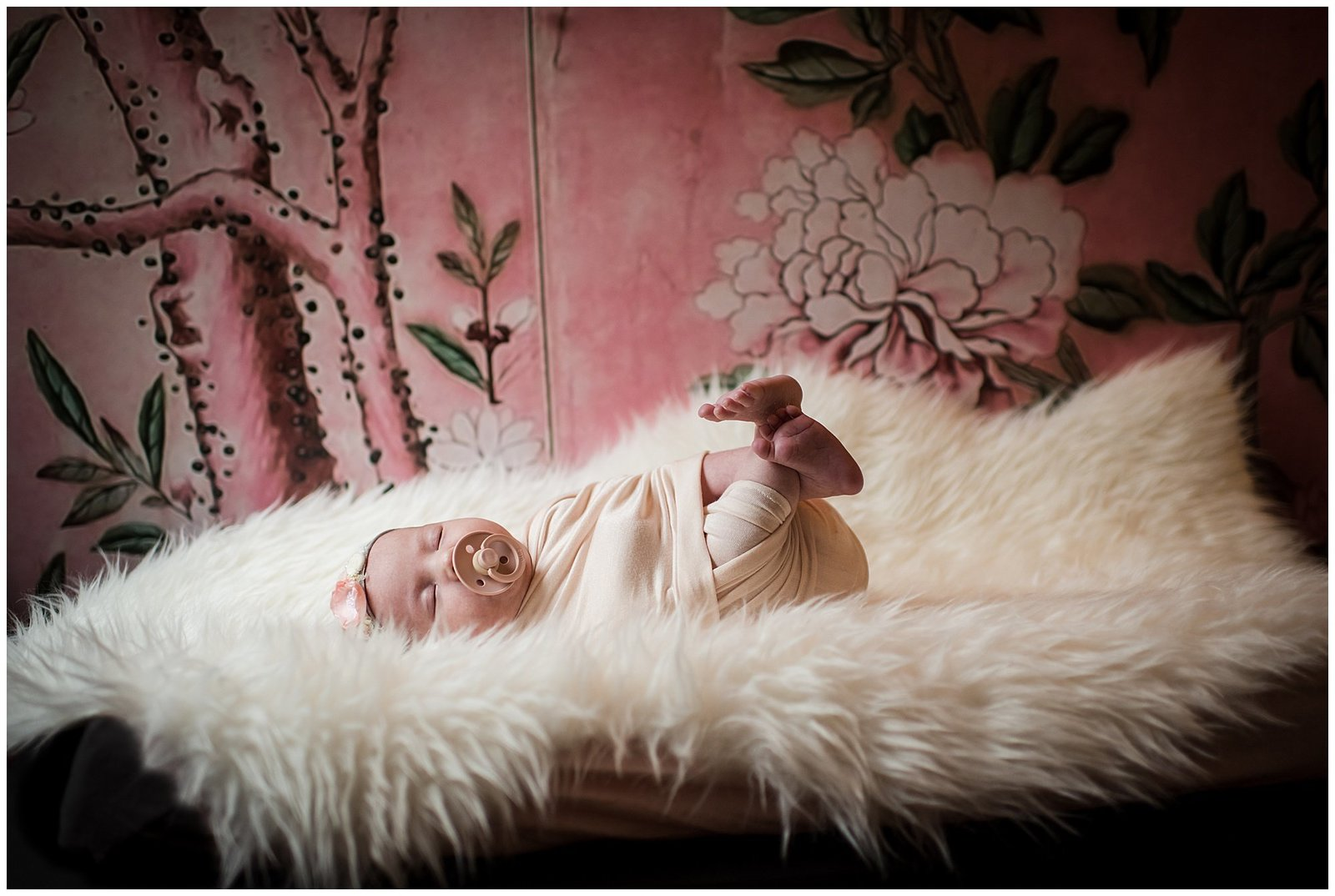 Newborn baby girl on sheepskin with pink floral Magnolia wallpaper moody Emily Ann Photography Seattle Photographer