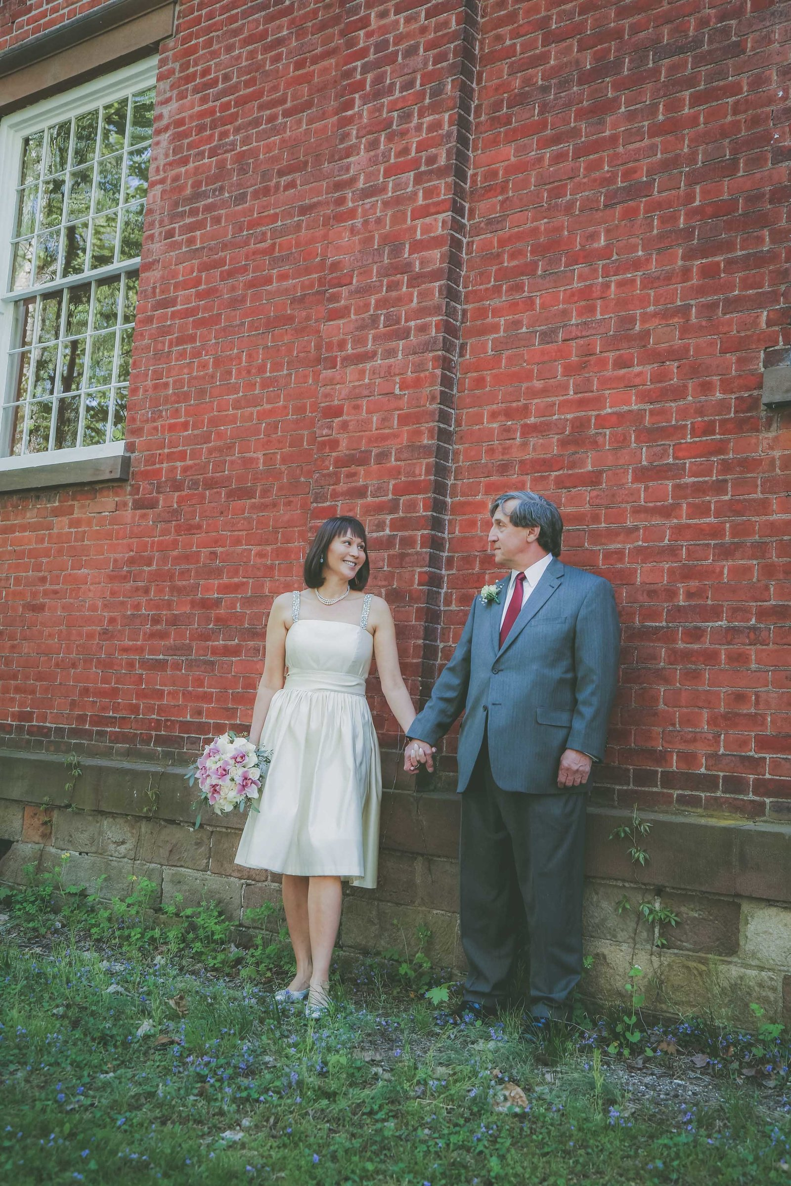 Wedded couple holds hands against a brick building in NJ.