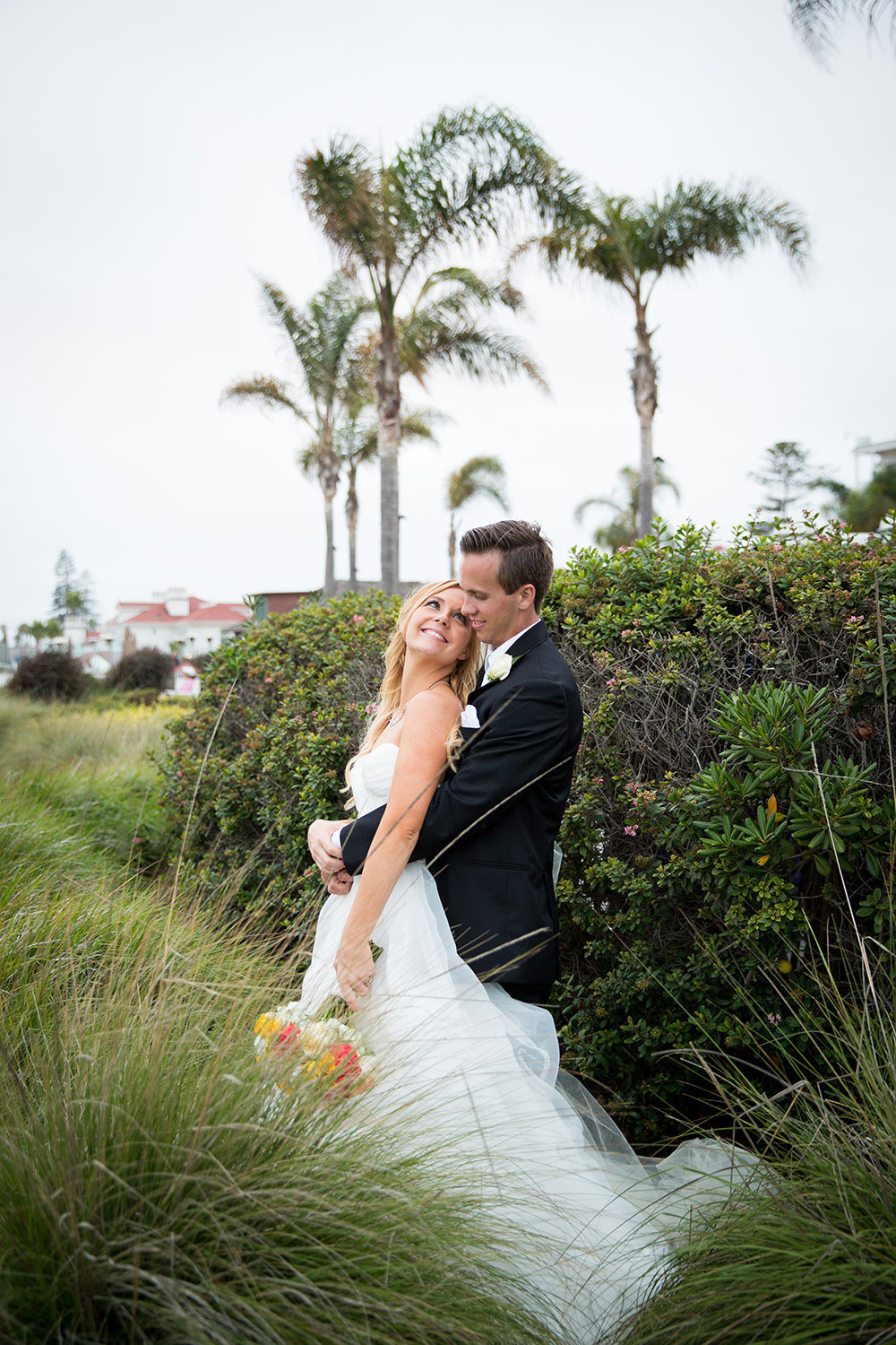 Bride and groom wedding portrait in tall grass at the sand dunes in Coronado